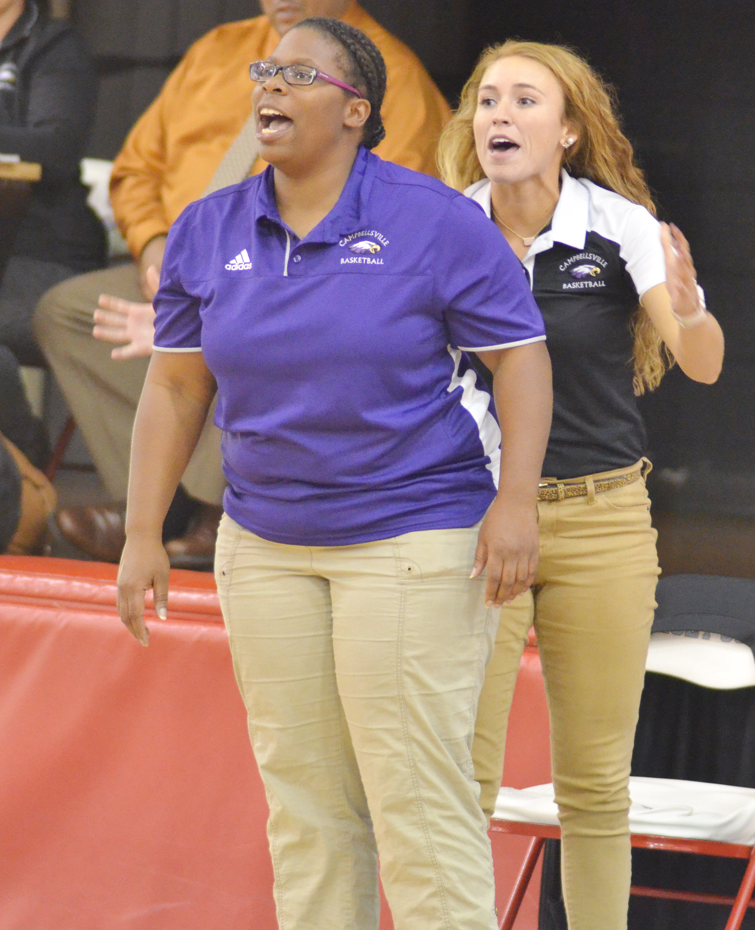 CMS head girls' basketball coach Tiarra Cecil yells to her players as assistant coach LeeAnn Grider jumps behind her.