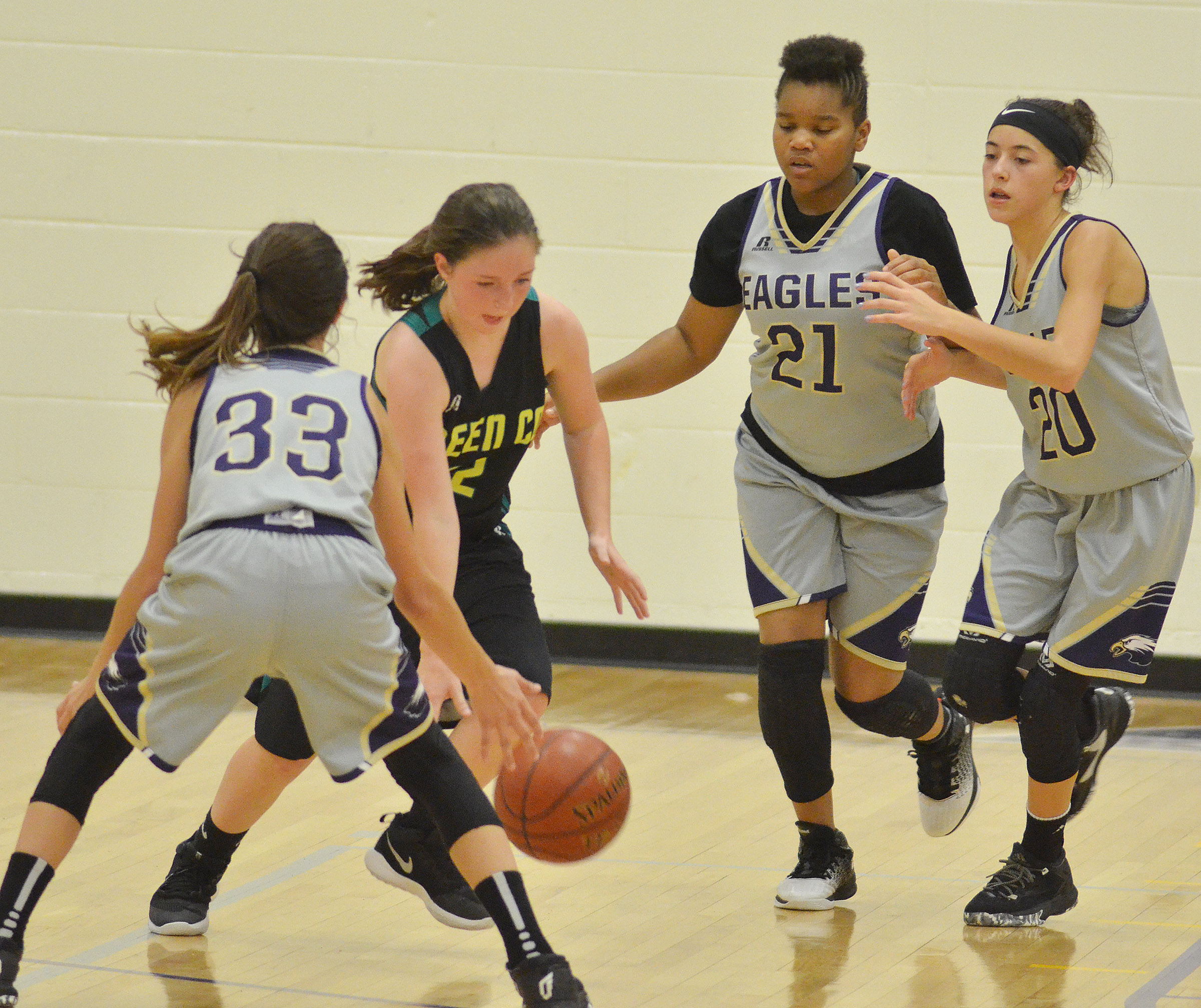 CMS seventh-graders Bri Hayes, at left, and Antaya Epps, at right, and eighth-grader Kaylyn Smith play defense.