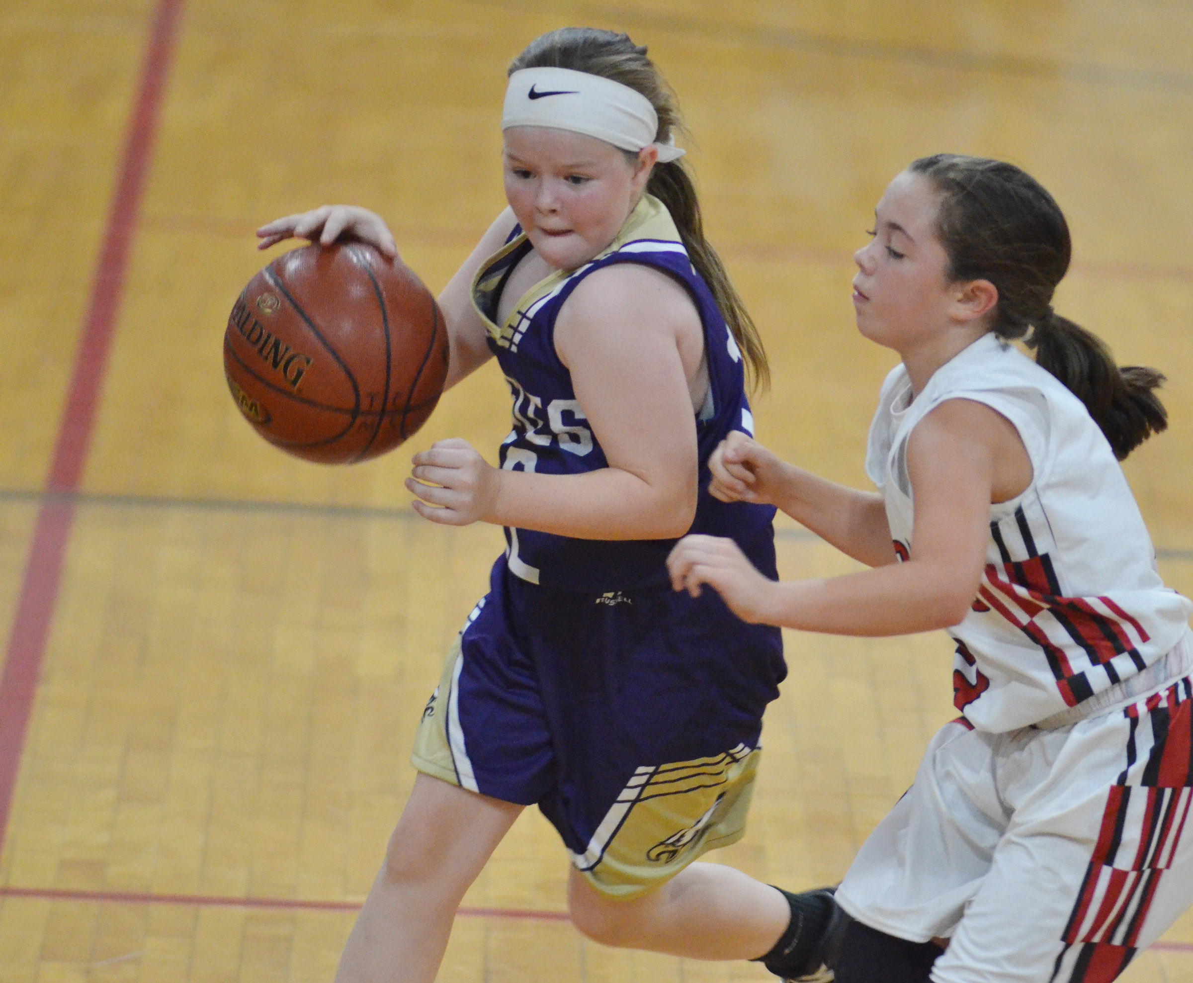 Campbellsville Elementary School fifth-grader Miley Hash dribbles around a Taylor County defender.