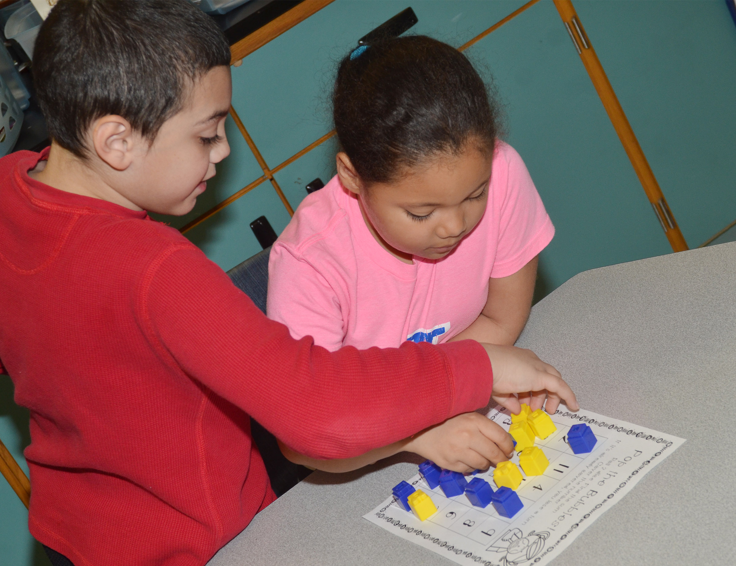 CES first-graders Diego Aquino, at left, and Briana Wooley play a Pop the Bubble counting game.