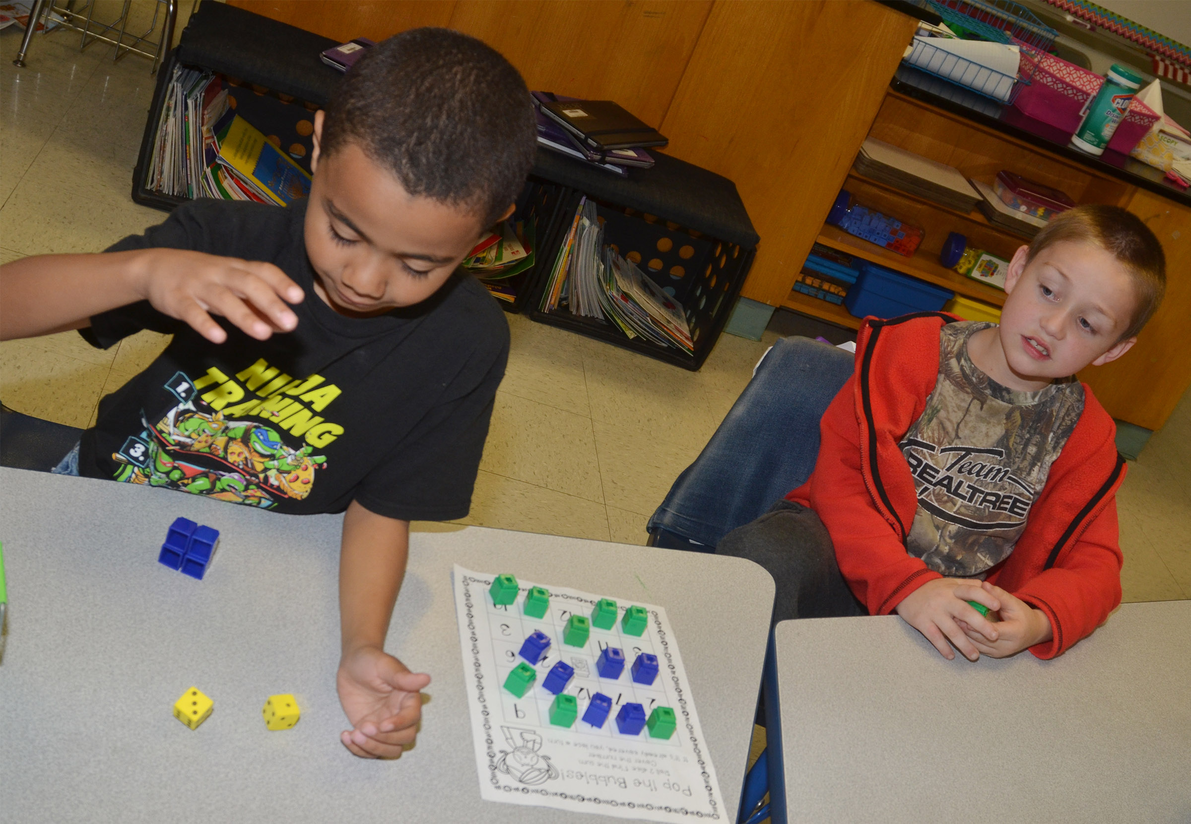 CES first-graders Trace Richardson, at left, and Jacob Golden play a Pop the Bubble counting game.