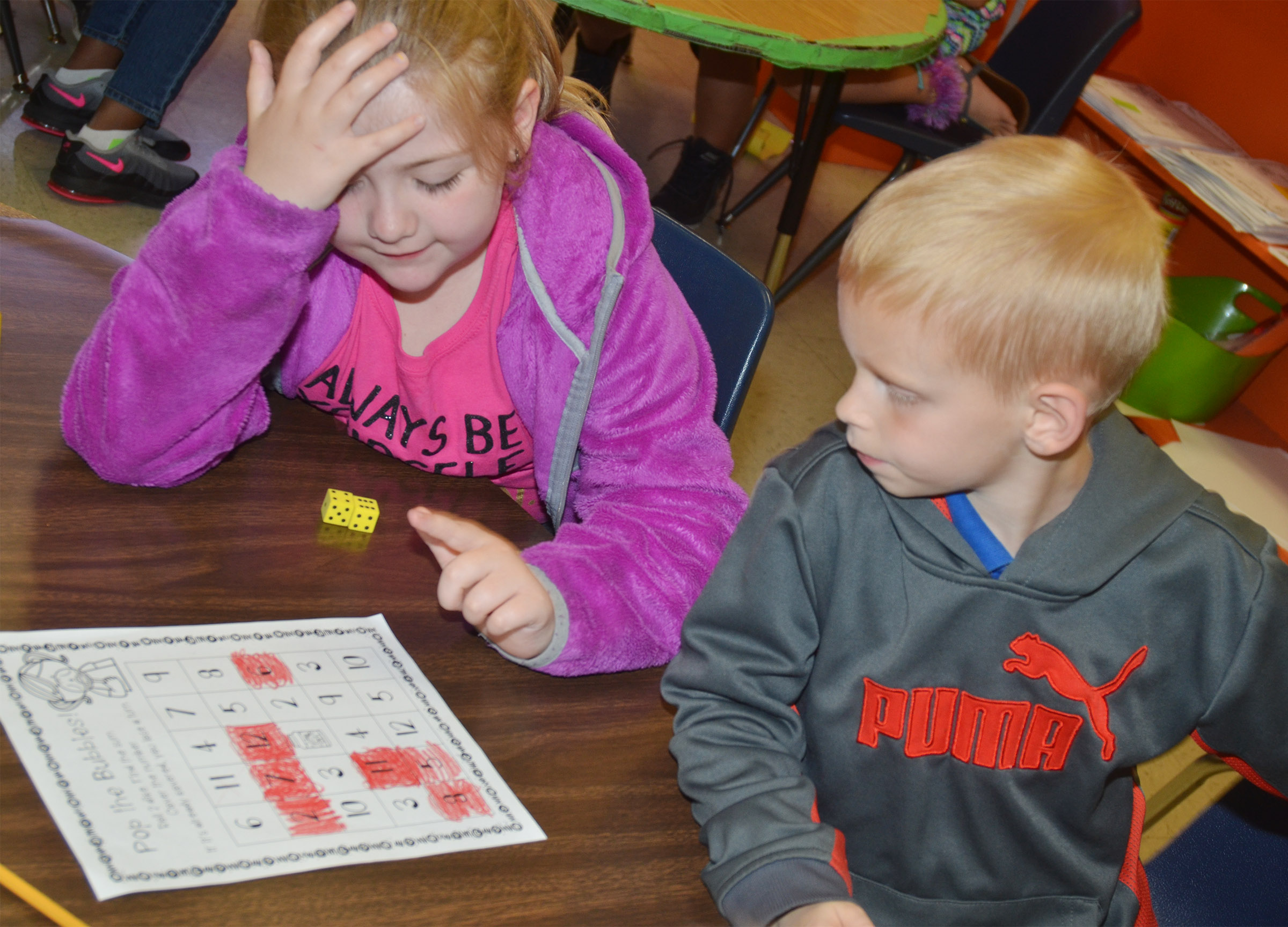 CES first-graders London Whitlow, at left, and Chase Gabbert play a Pop the Bubble counting game.