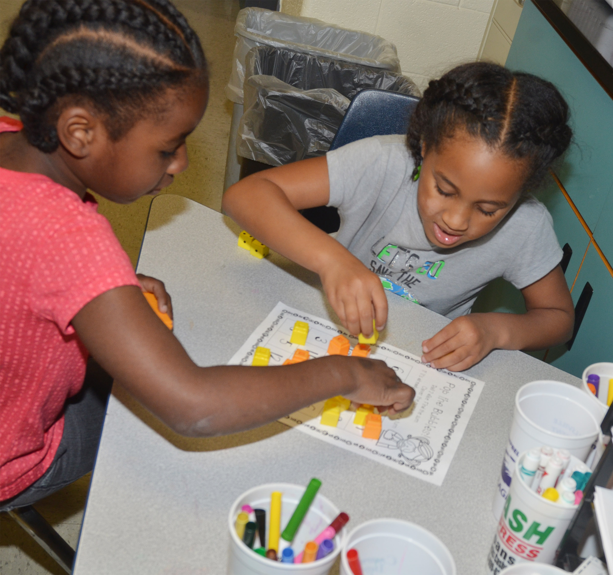 CES first-graders Destini Gholston, at left, and Kadance Ford play a Pop the Bubble counting game.