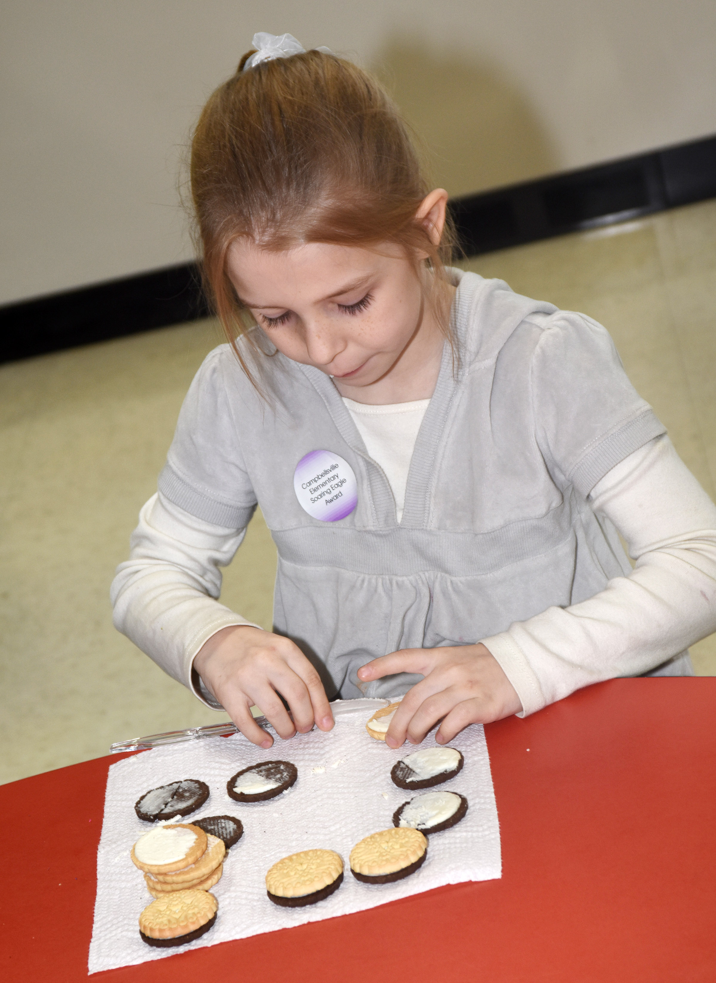 CES first-grader Madison Walters makes the phases of the moon by using cream filled cookies.