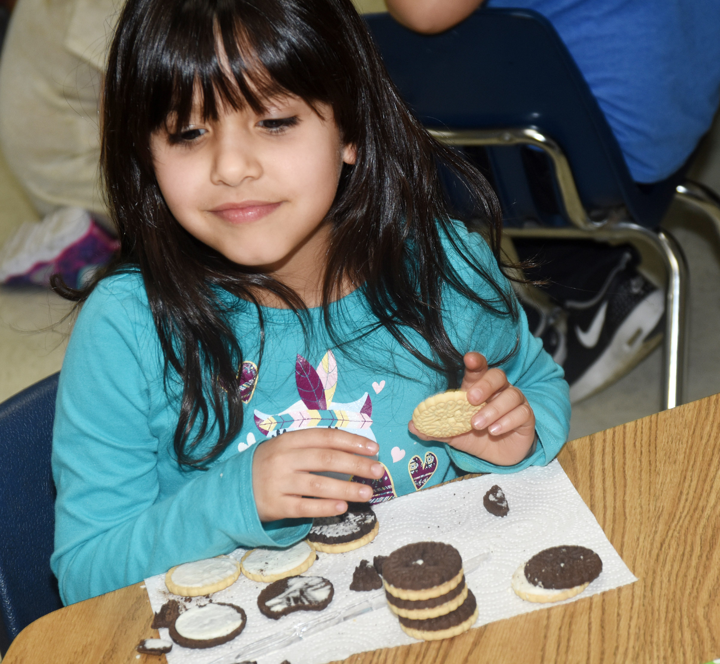 CES first-grader Carol Moura makes the phases of the moon by using cream filled cookies.