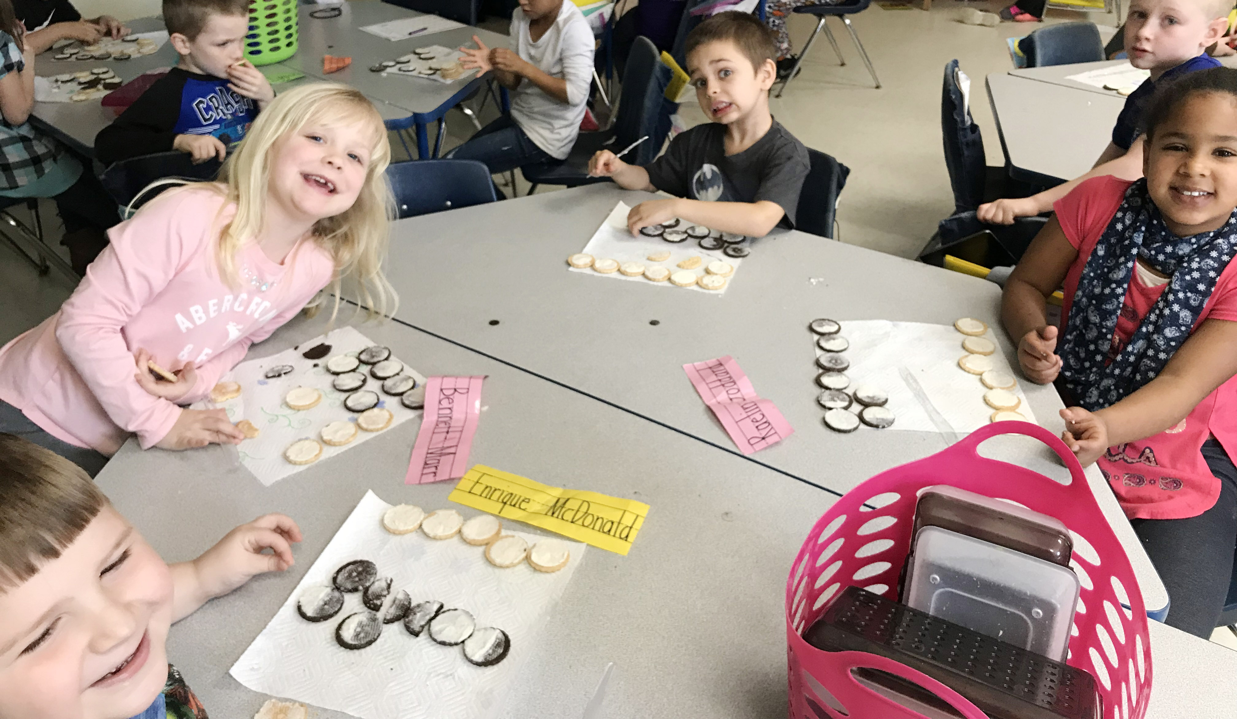 CES first-graders, from left, Enrique McDonald, Ava Bennett-Marr, Michael Terry and Raelin Goddard make the phases of the moon by using cream filled cookies.