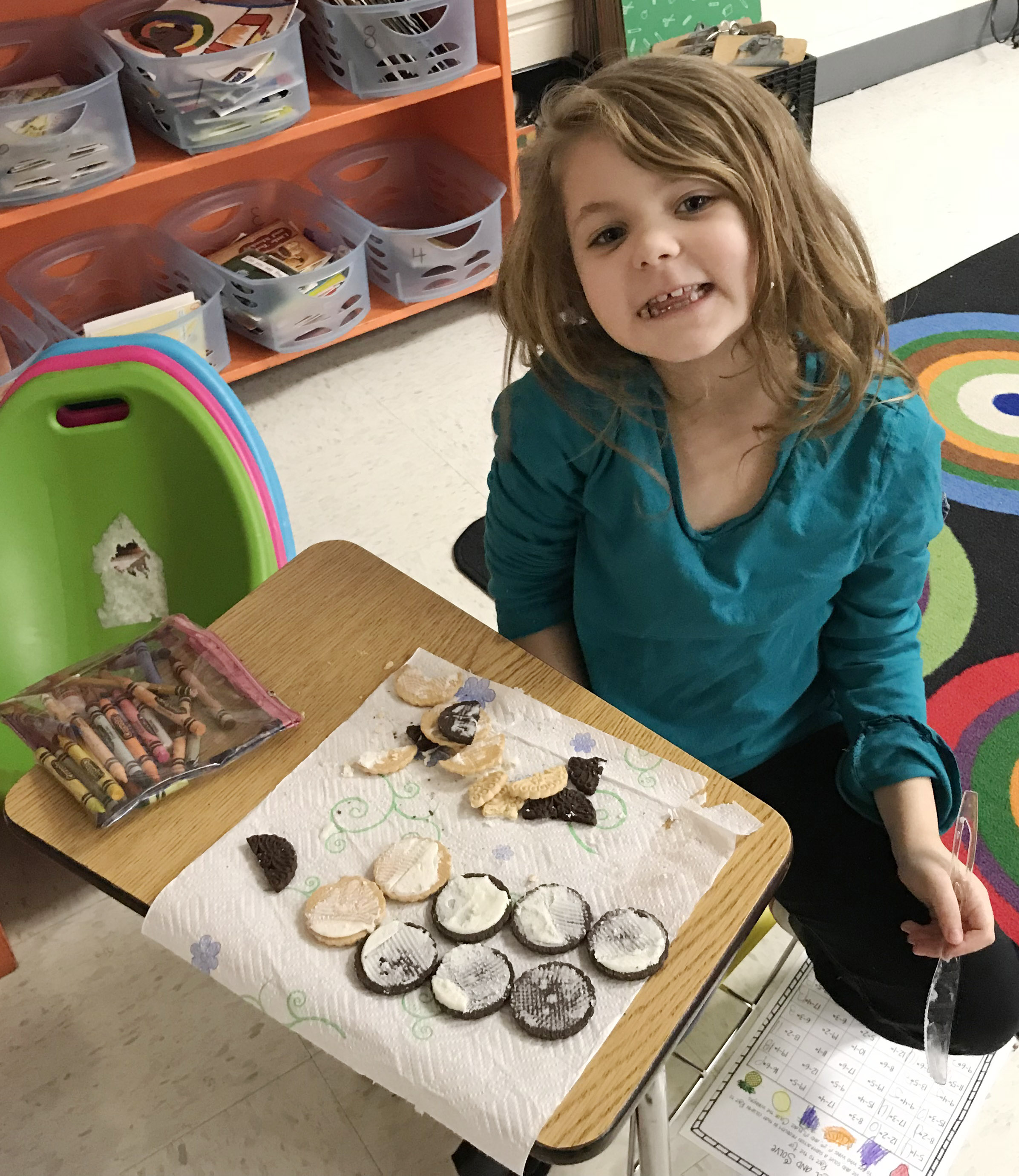 CES first-grader Aubrey Wilson makes the phases of the moon by using cream filled cookies.