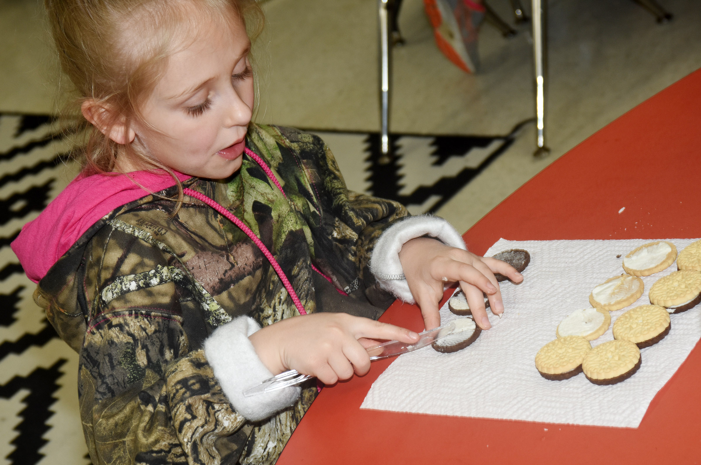 CES first-grader LeeAnna Garvin makes the phases of the moon by using cream filled cookies.