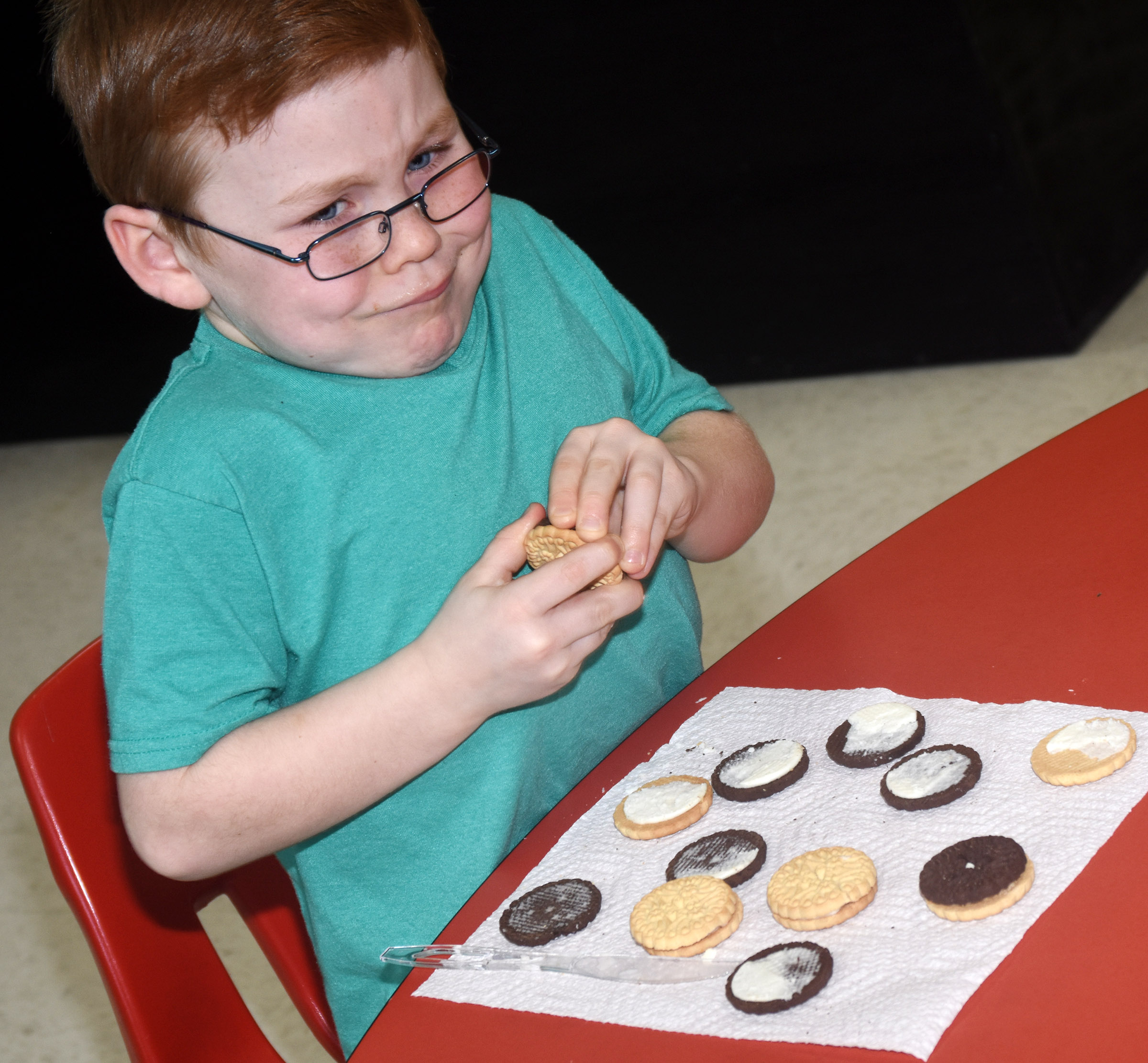 CES first-grader Daven Davis tries to open a cookie so he can make the phases of the moon.