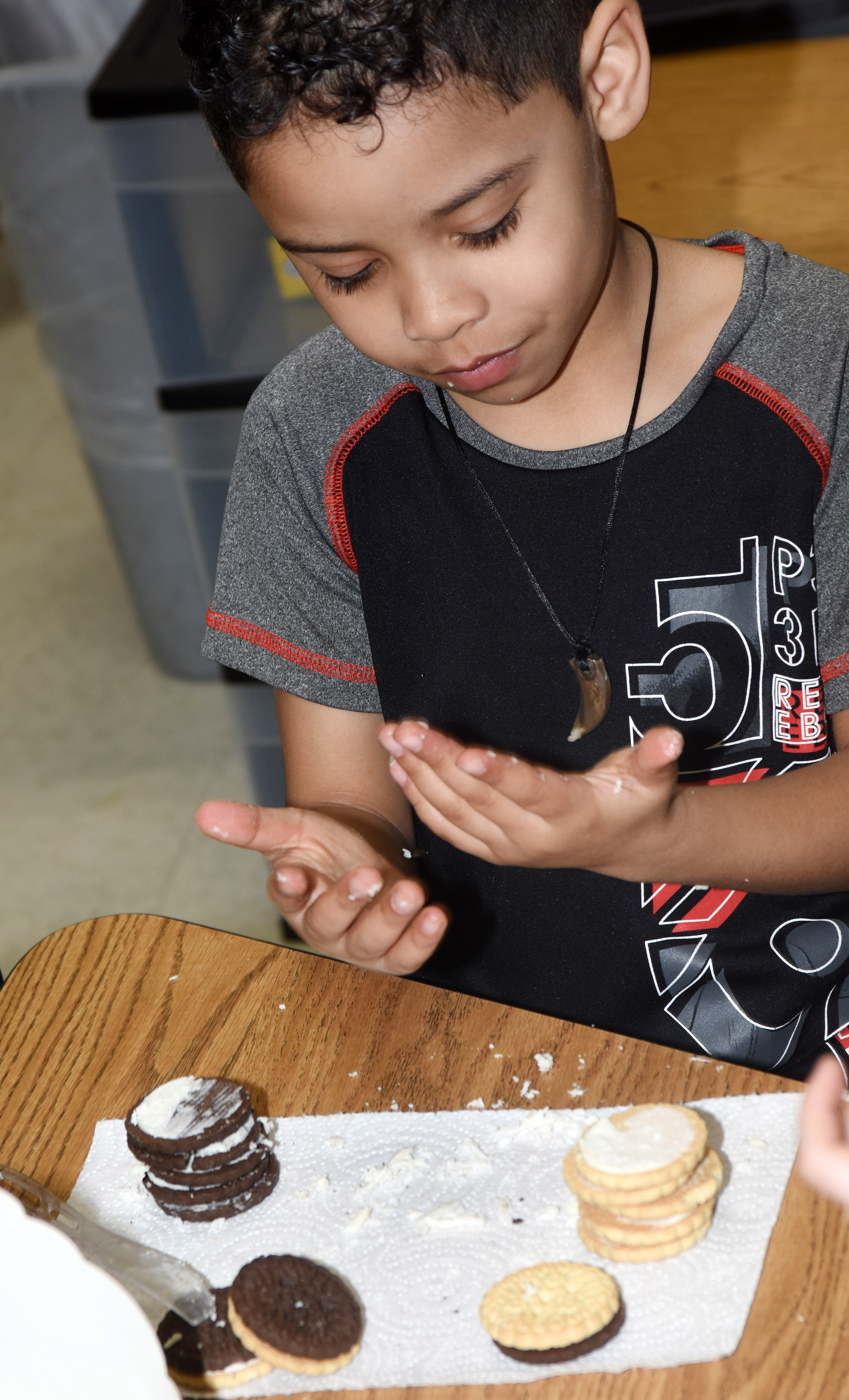 CES first-grader Demarcus Noyola makes the phases of the moon by using cream filled cookies.