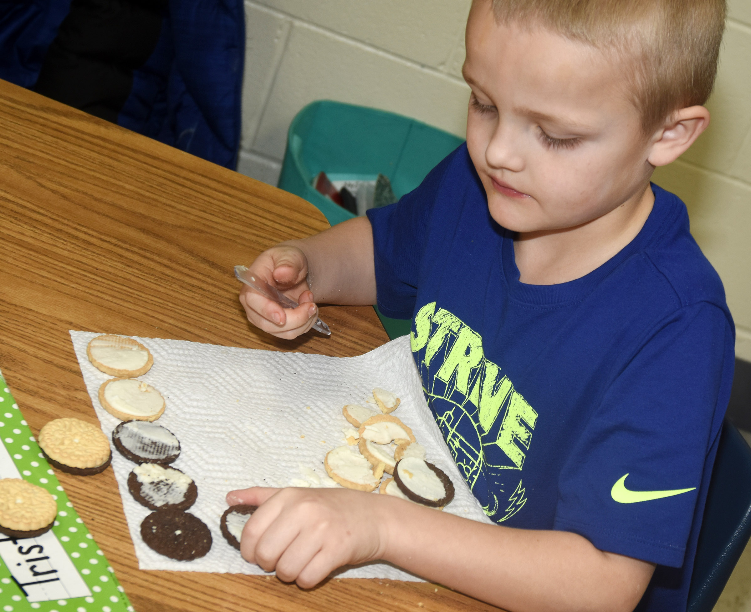 CES first-grader Tristian Harris makes the phases of the moon by using cream filled cookies.