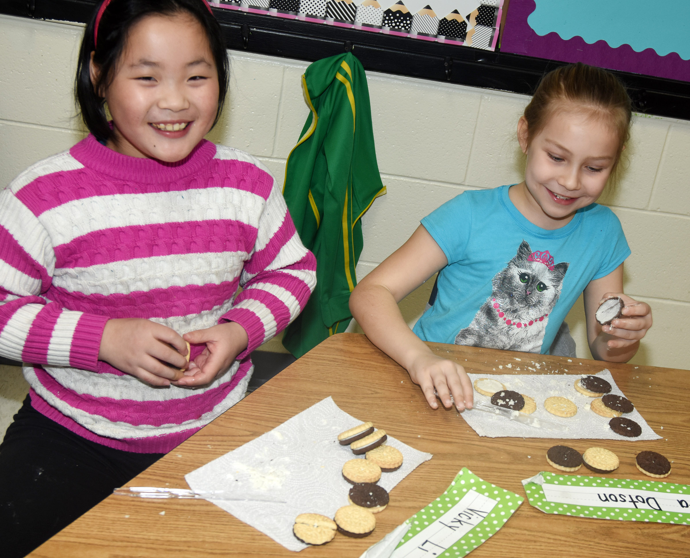 CES first-graders Vicky Li, at left, and Kira Dotson makes the phases of the moon by using cream filled cookies.