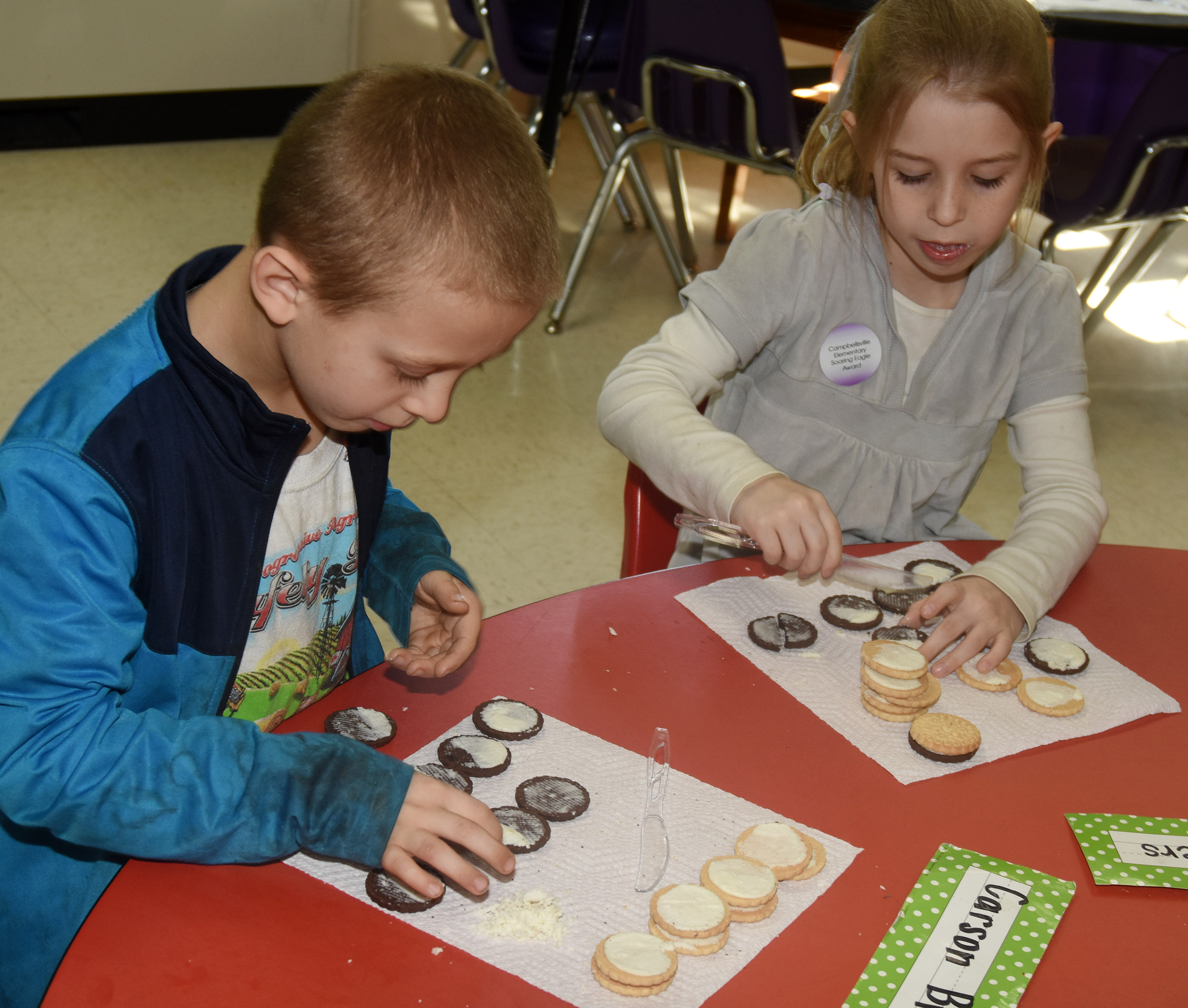 CES first-graders Carson Brown, at left, and Madison Walters make the phases of the moon by using cream filled cookies.