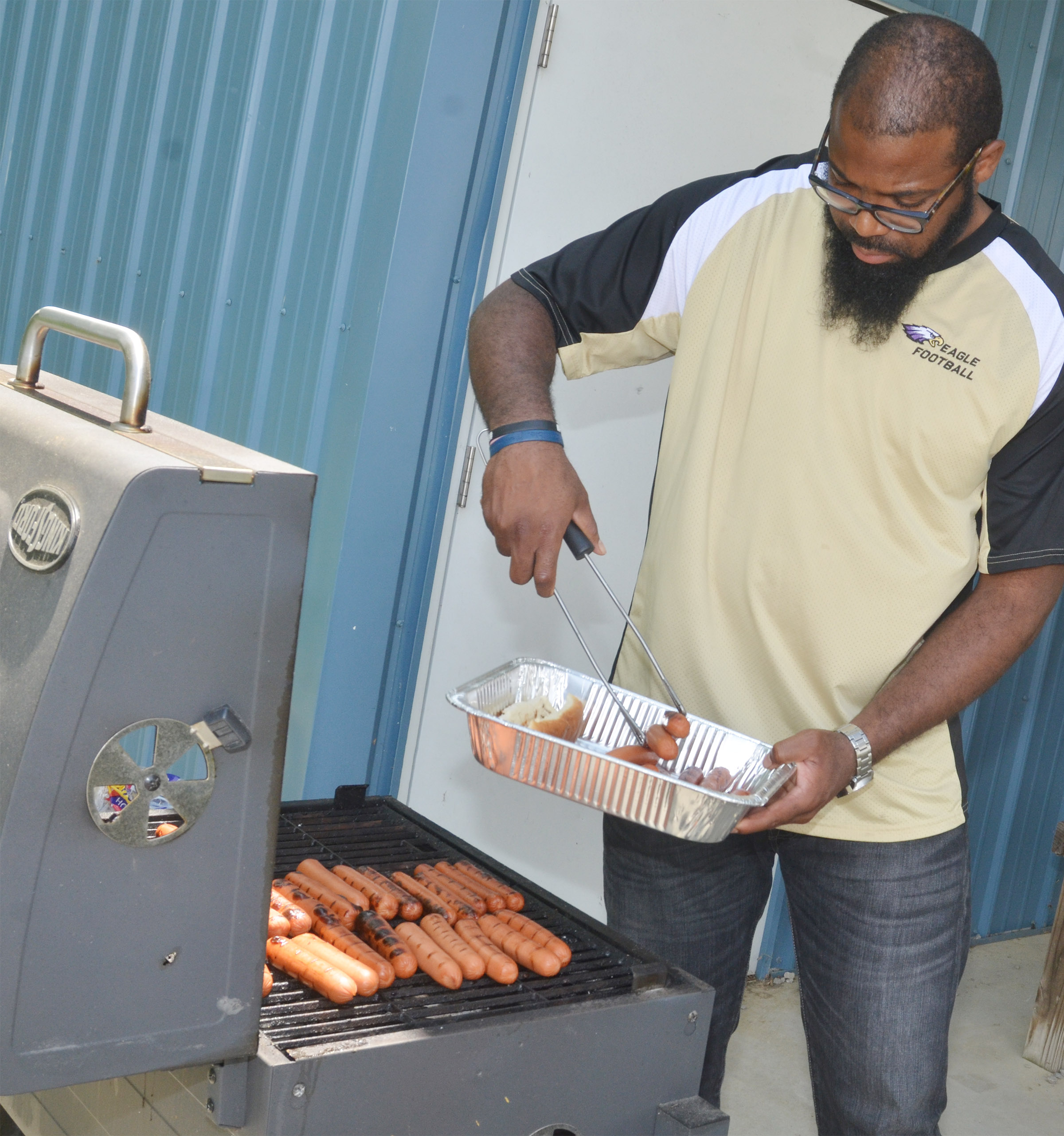 CES exceptional child educator Will Griffin cooks hot dogs for first-grade students.