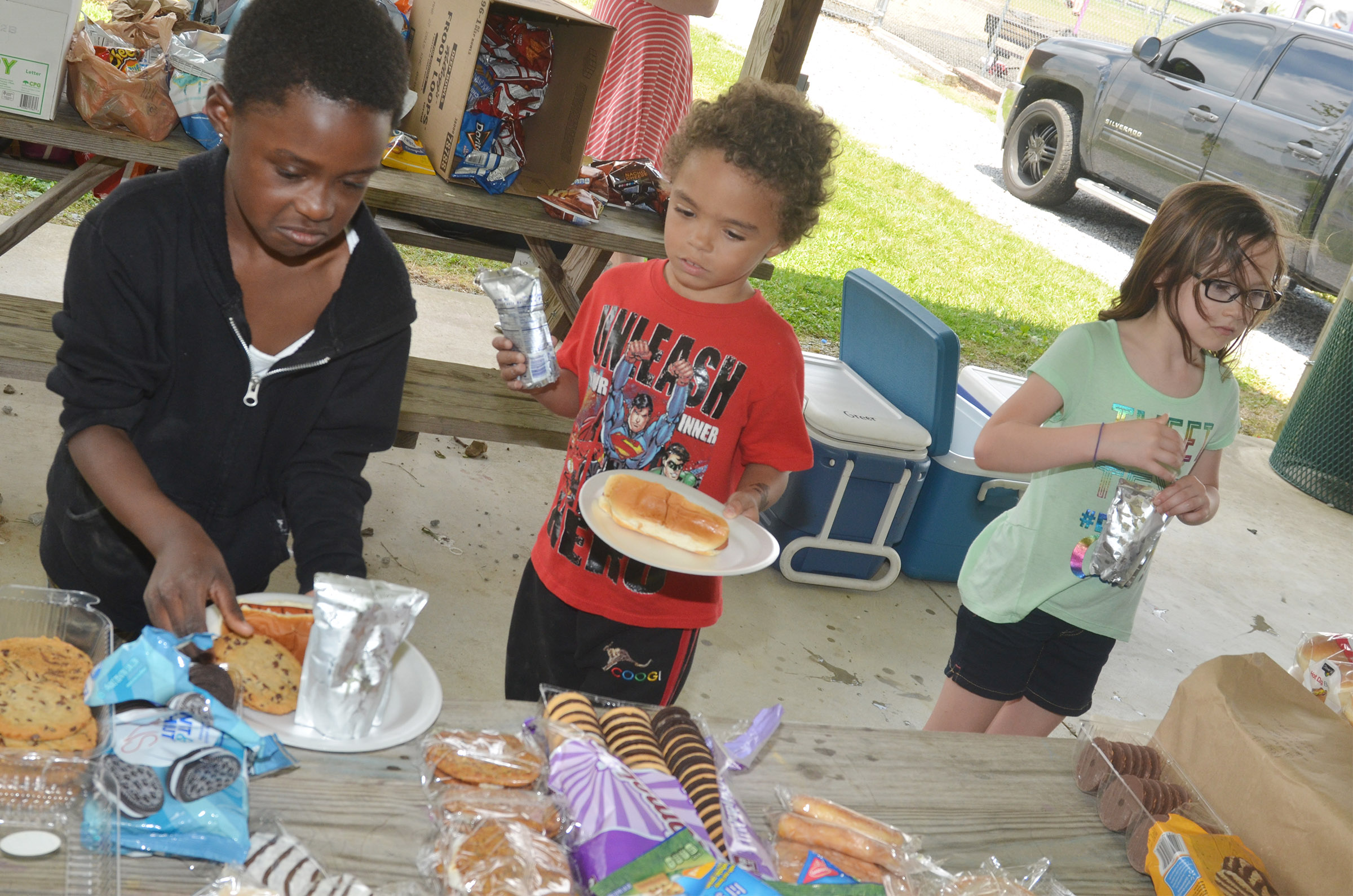 CES first-graders Zion Mitchell, at left, and Javion Milby get food at their cookout.
