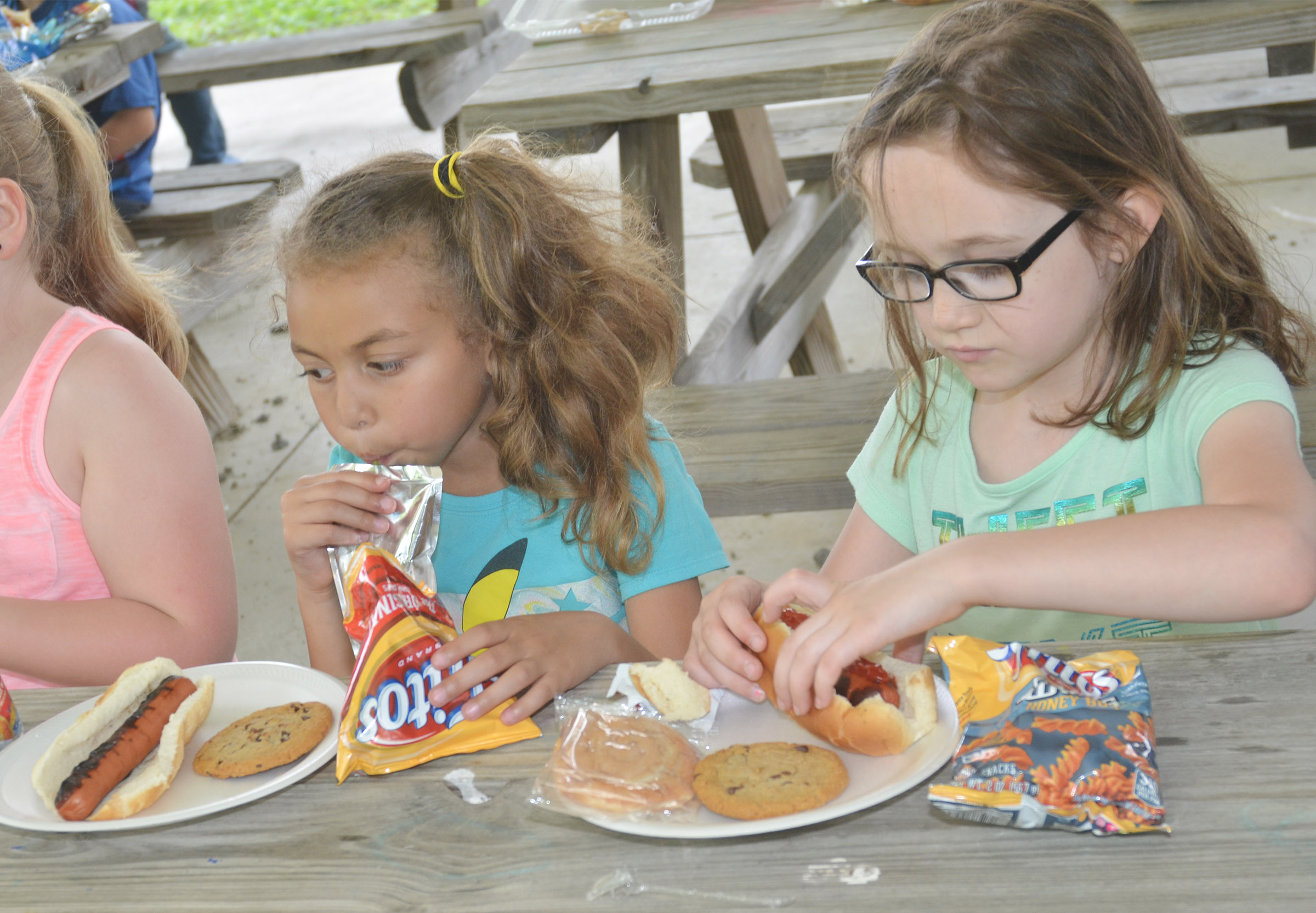 CES first-graders Londyn Smith, at left, and Frehley Whitlow enjoy their cookout.