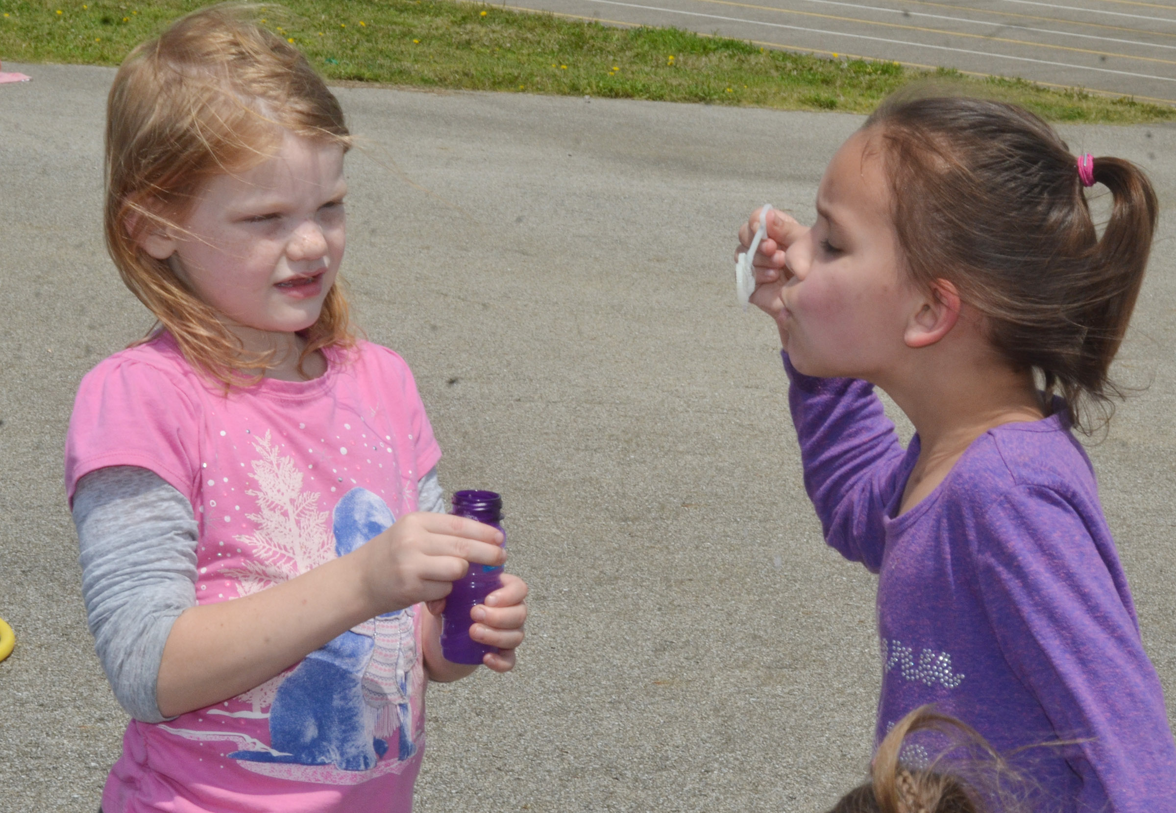 CES first-graders Gracie Wooley, at left, and Adriana Agent blow bubbles together.