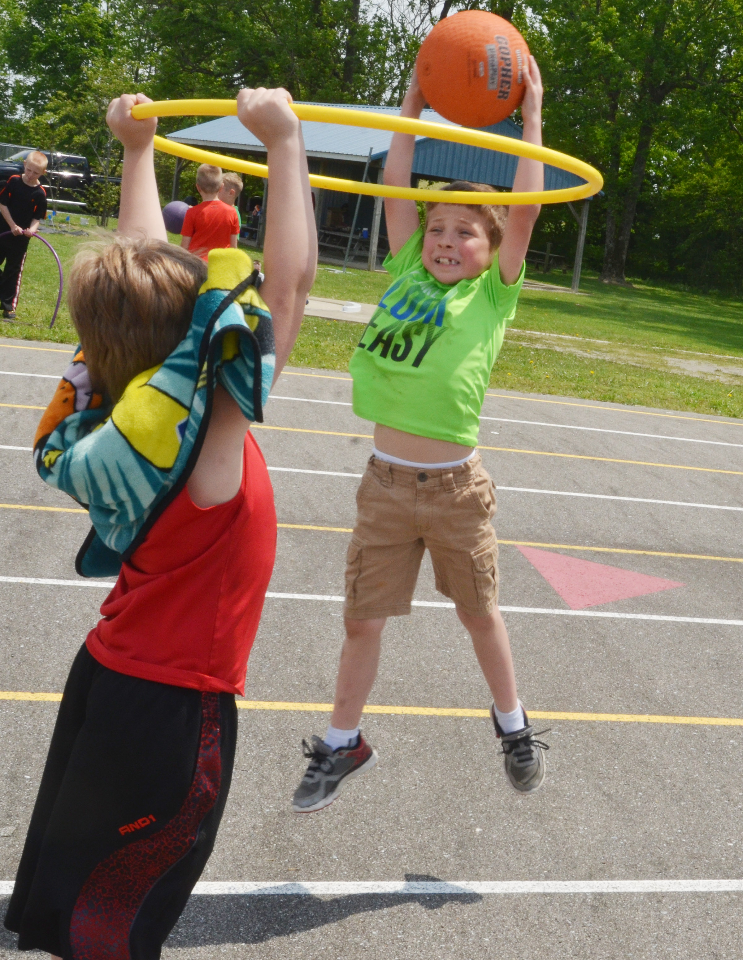 CES first-grader Bryson Gabehart jumps to shoot a basketball in a hula hoop.