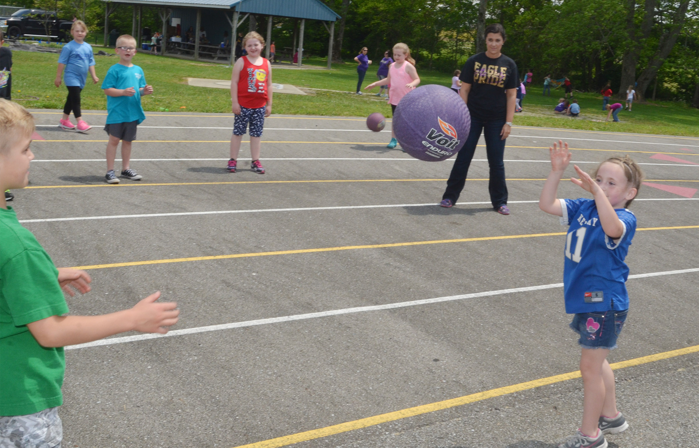 CES first-graders play catch with teacher Hailey Ogle.