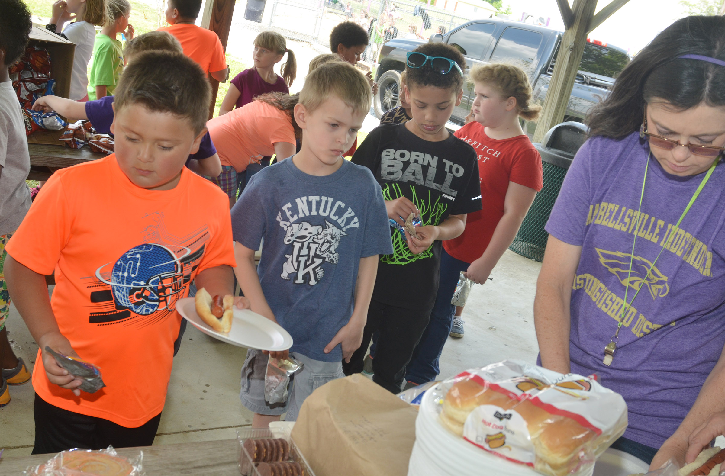 CES first-grade teacher Shirley Cox serves, from left, Alex Mixtega, Logan Weddle and Bryant Mayo at their cookout.