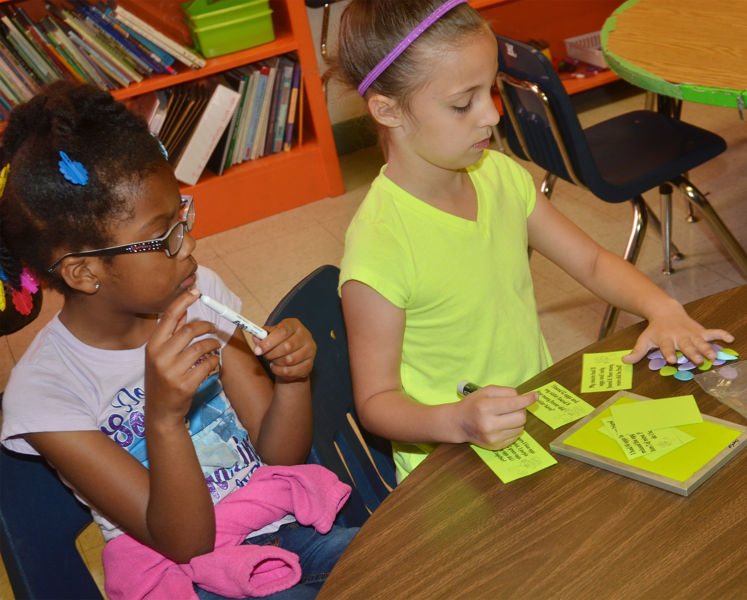 CES first-graders Willow Griffin, at left, and Lillian Martin work together to solve a math word problem.