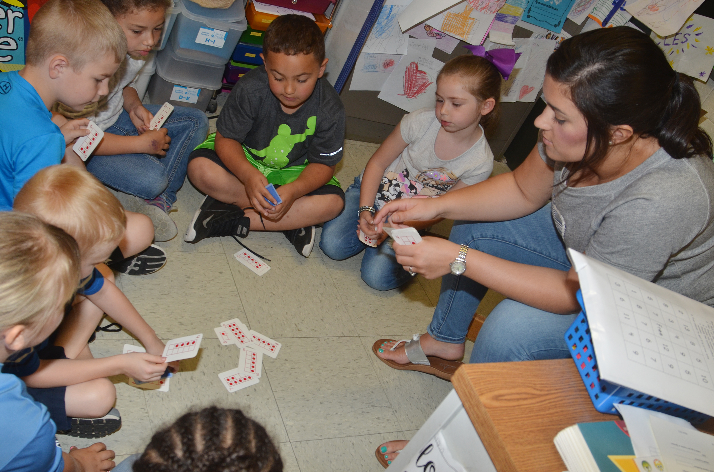 CES first-grade teacher Hailey Ogle plays a math card game with her students.