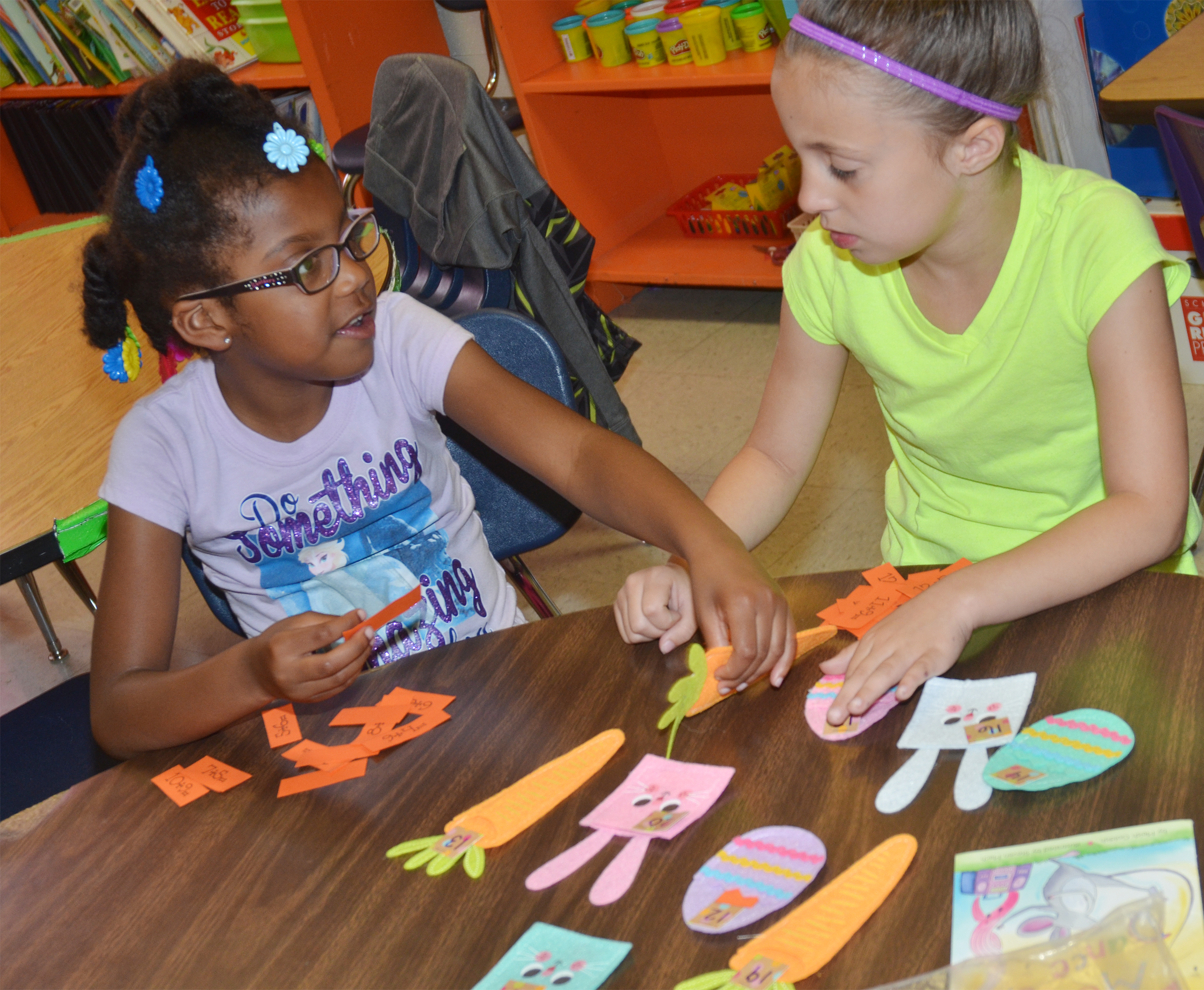 CES first-graders Willow Griffin, at left, and Lillian Martin solve a math problem.