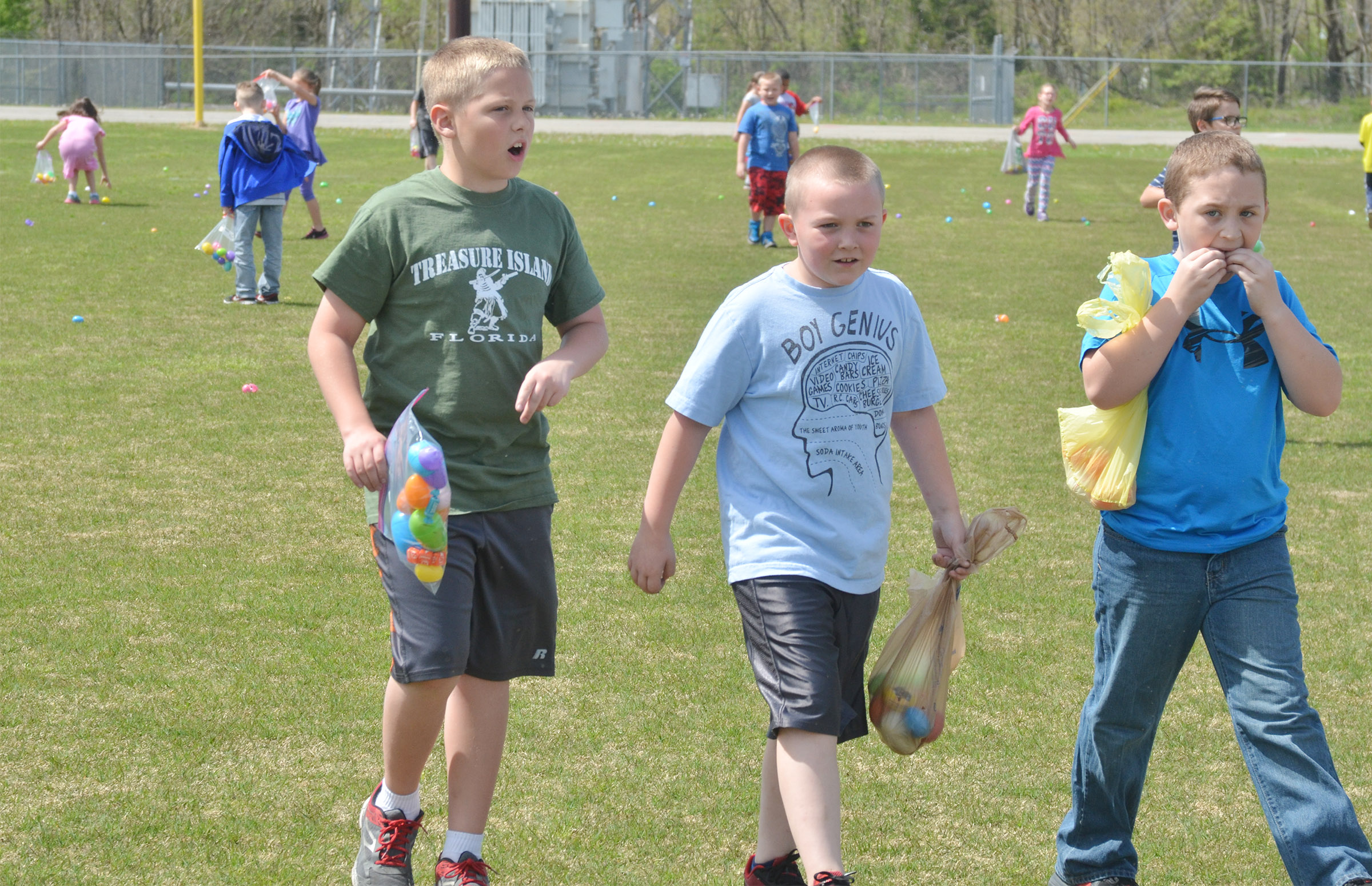 CES second-graders, from left, Evan Lockridge, Griffin Skaggs and Carson Ford search for Easter eggs.