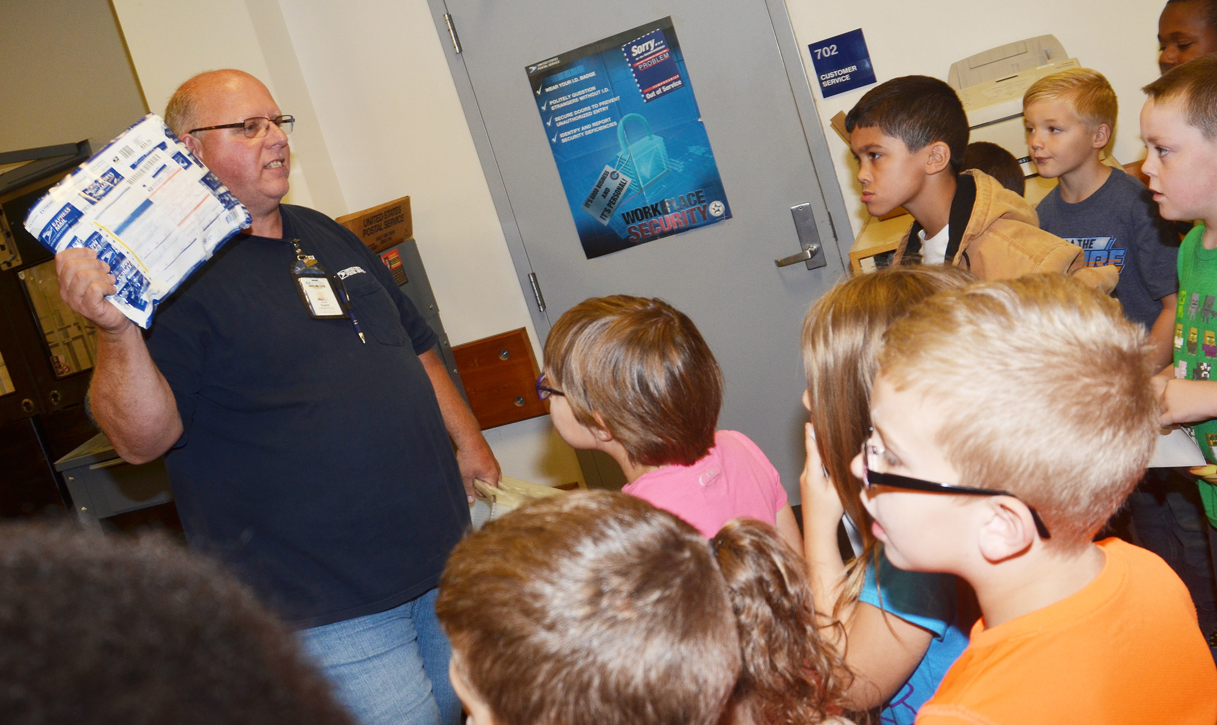 Campbellsville Post Office employee Scott Darst talks to CES students about how packages are sorted.