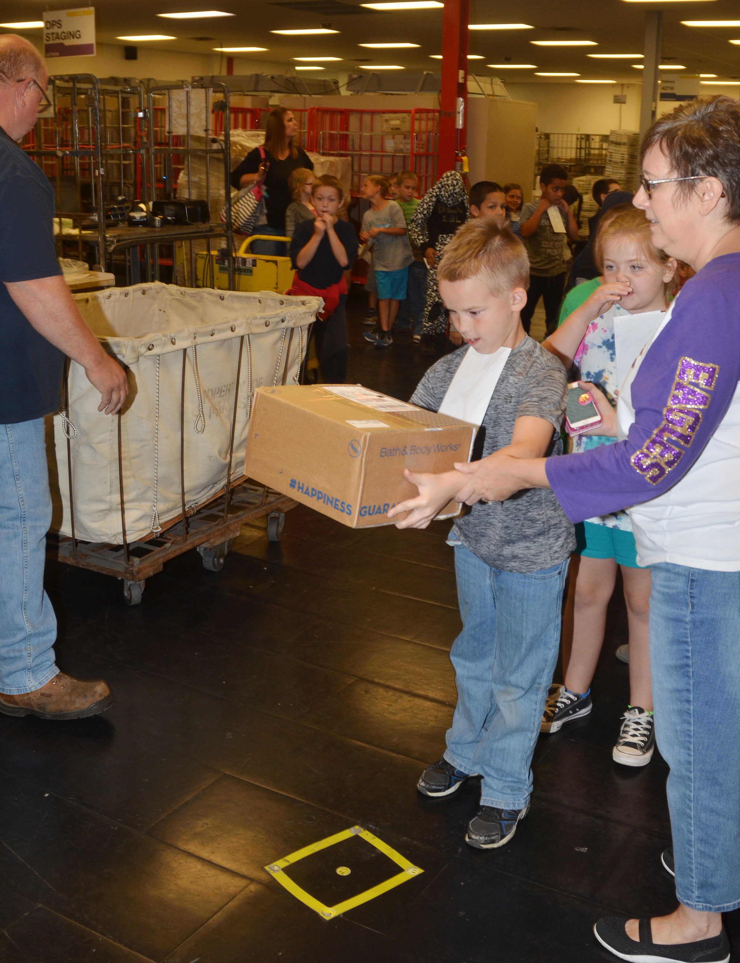 CES second-grader Jackson Bates scans a package with a robot.