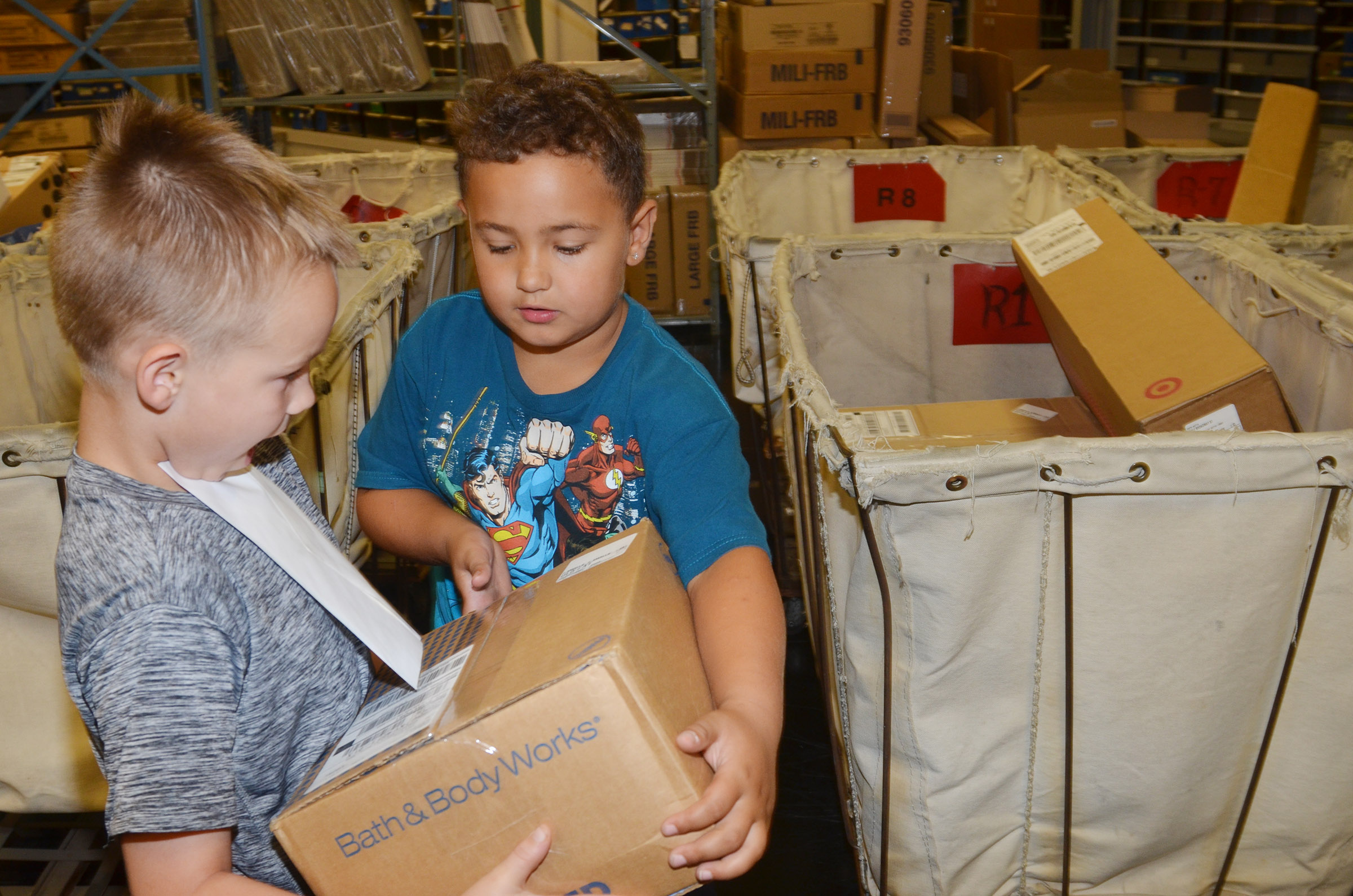 CES second-graders Jackson Bates, at left, and Marion Mann place a package into a bin corresponding with its route.