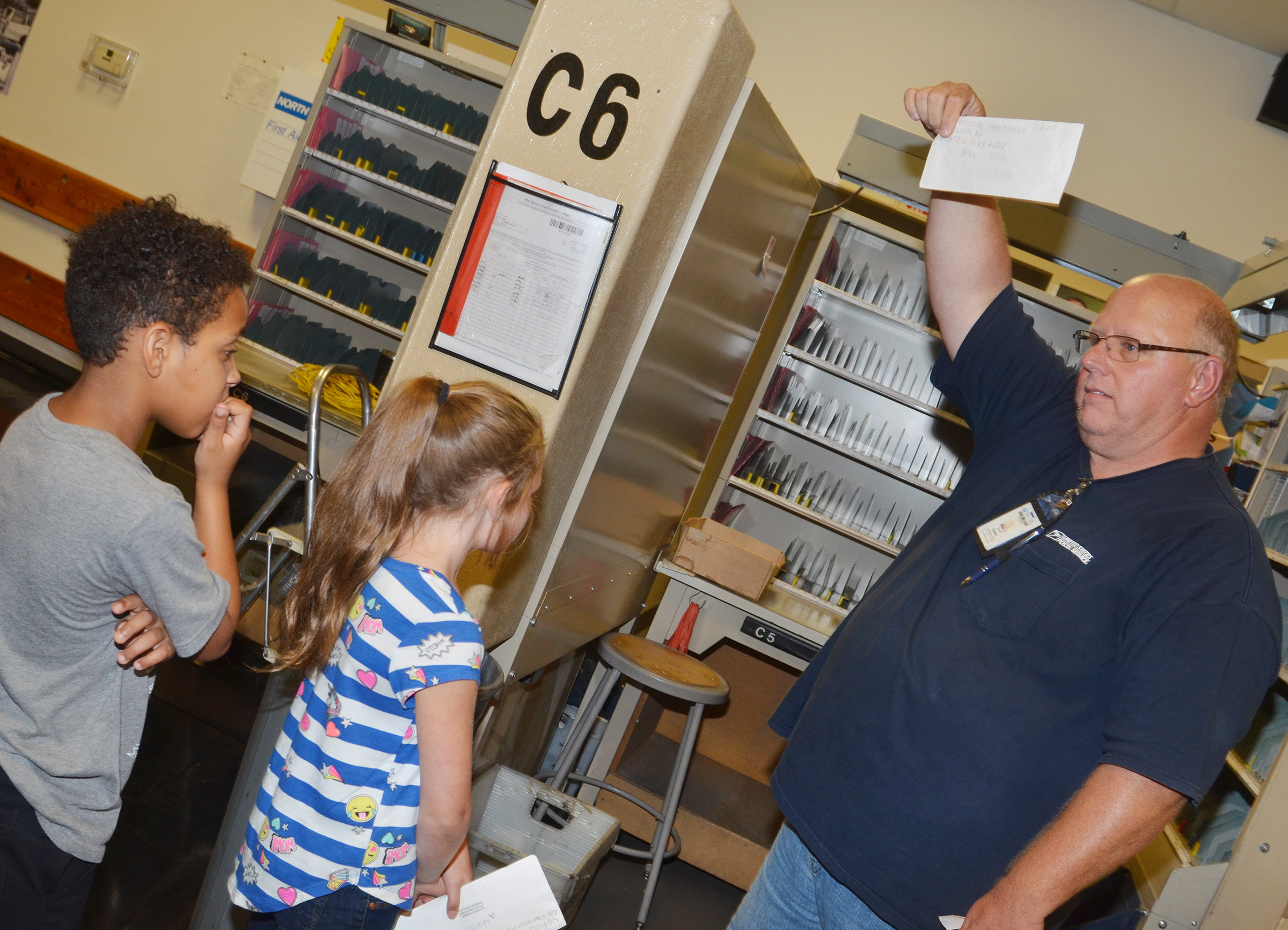 Campbellsville Post Office employee Scott Darst talks to CES students about how letters are sorted so they can be delivered.