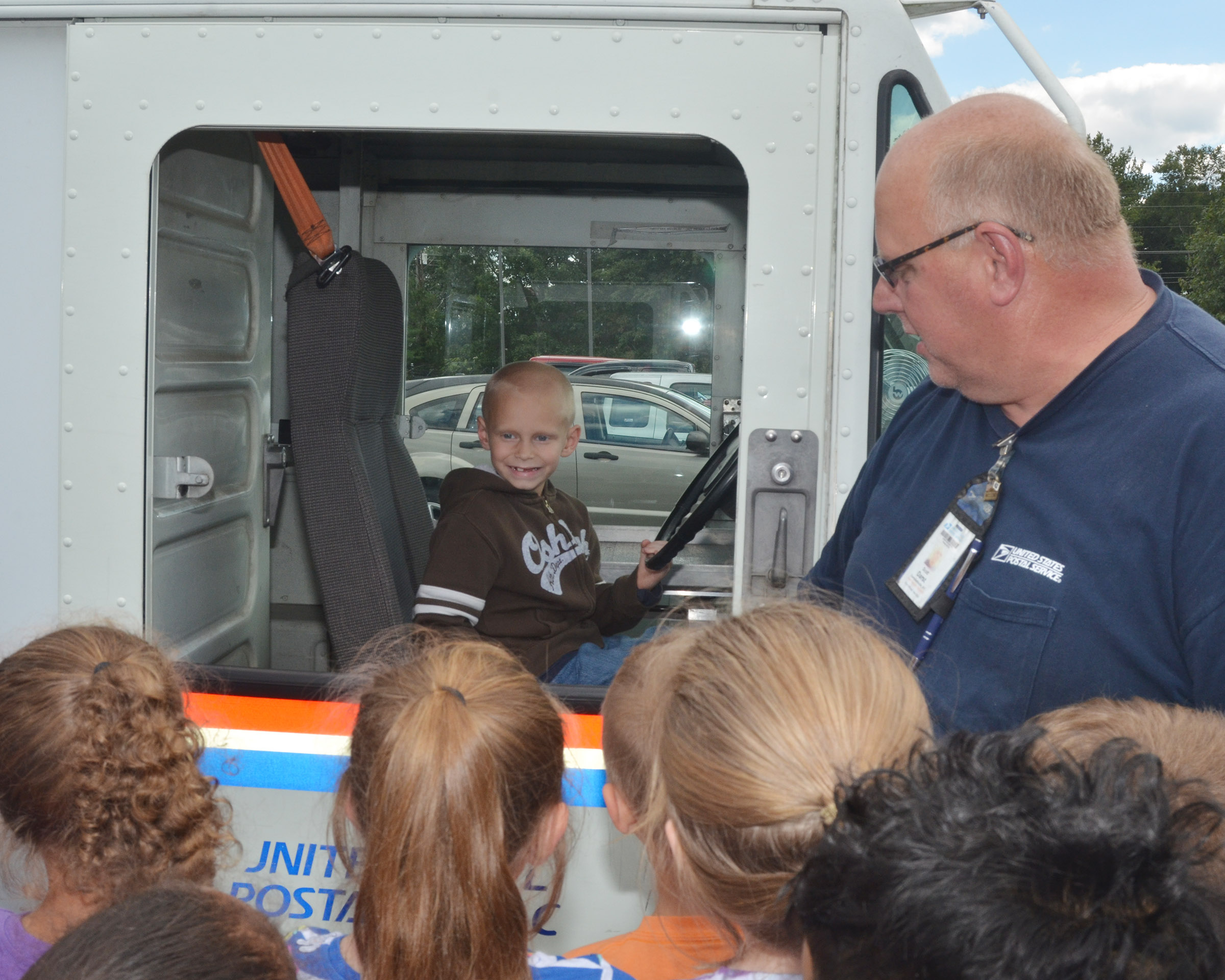 Campbellsville Post Office employee Scott Darst talks to CES second-graders about how drivers deliver mail, as Chase Gabbert sits in the driver's seat.
