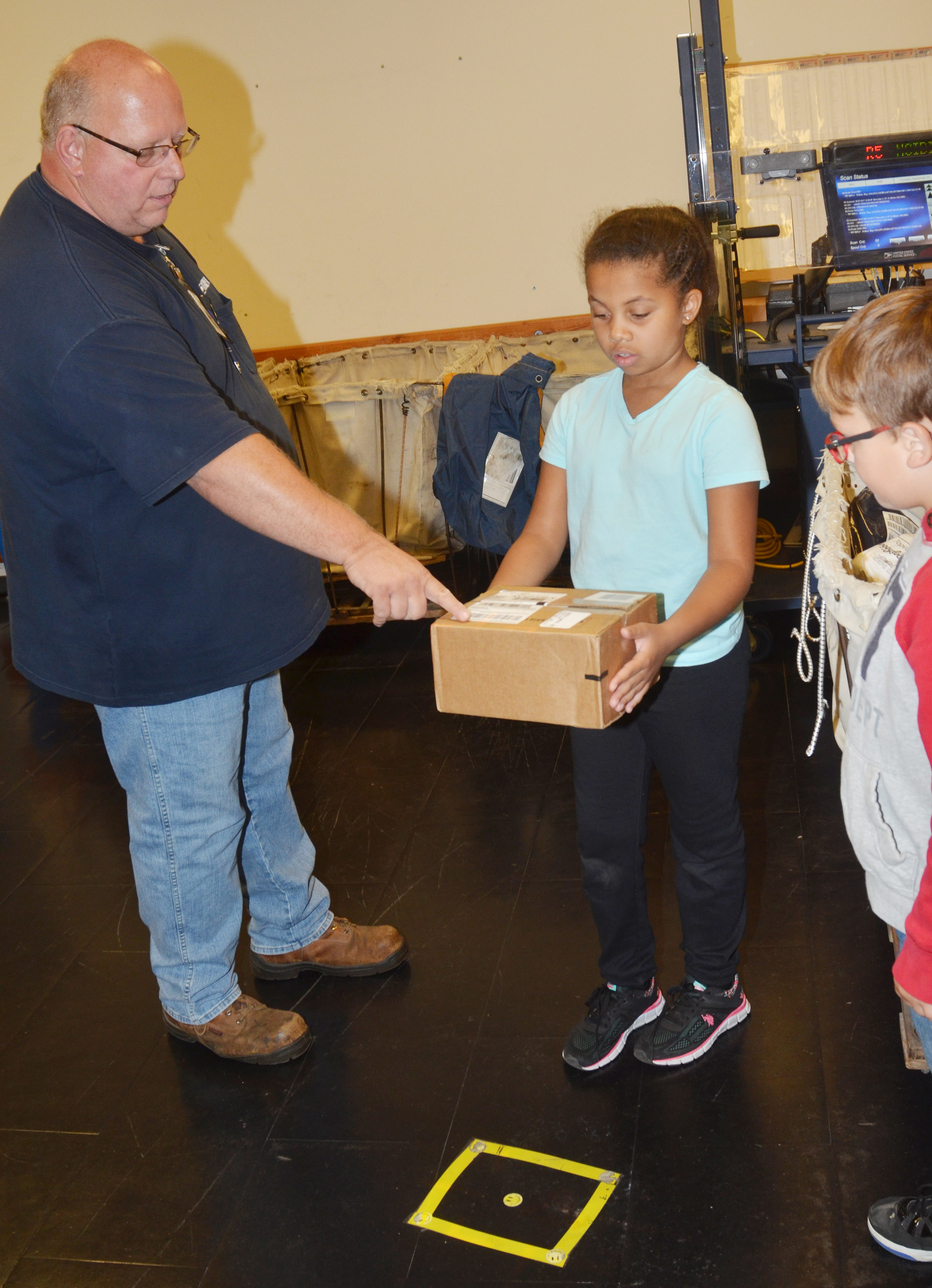 Campbellsville Post Office employee Scott Darst shows CES second-grader Journey Webb how a robot can scan a package and tell which route corresponds with its address.