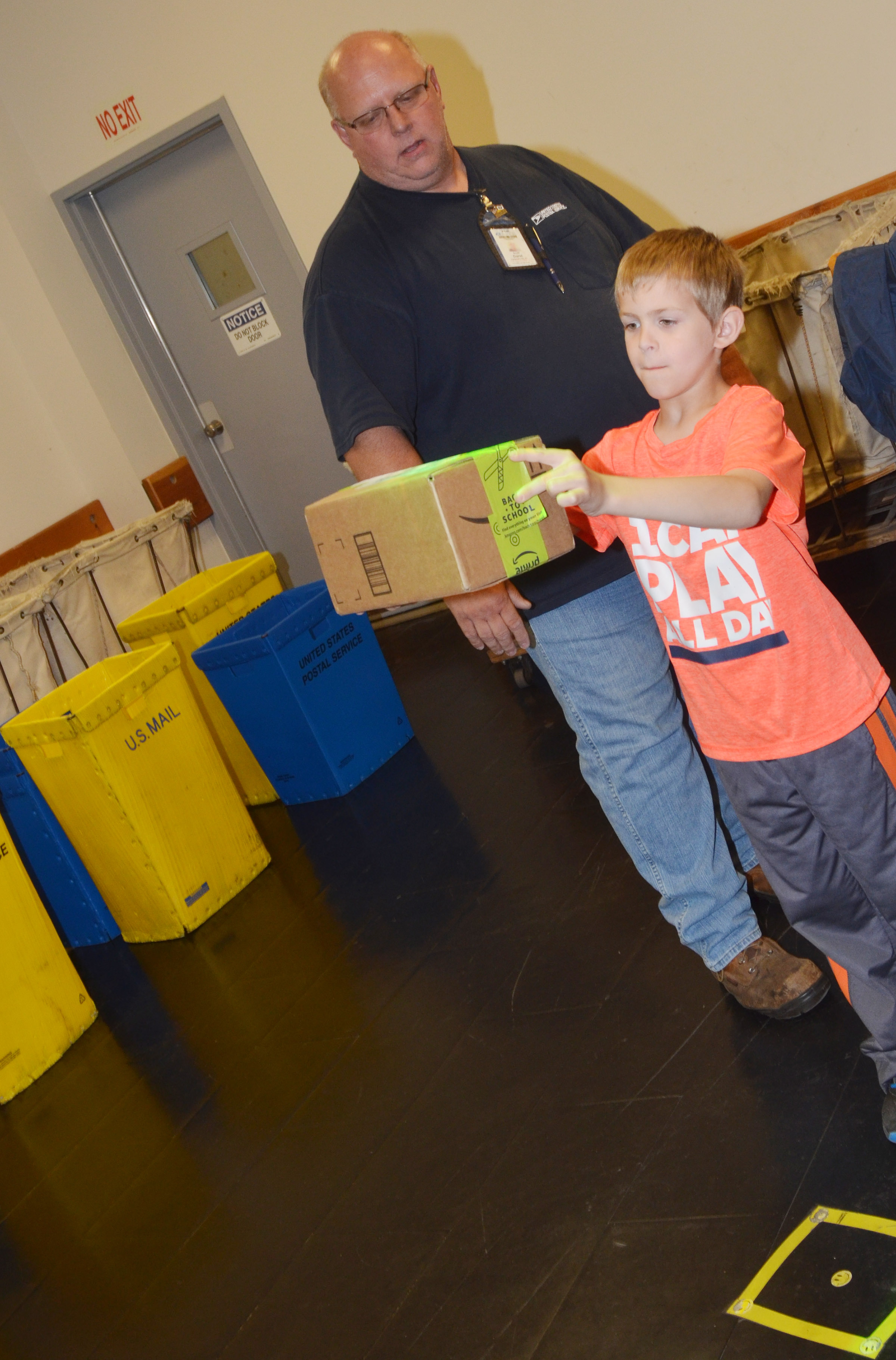 Campbellsville Post Office employee Scott Darst helps CES second-grader Logan Weddle scan a package using a robot to tell which route corresponds with the package's delivery address.