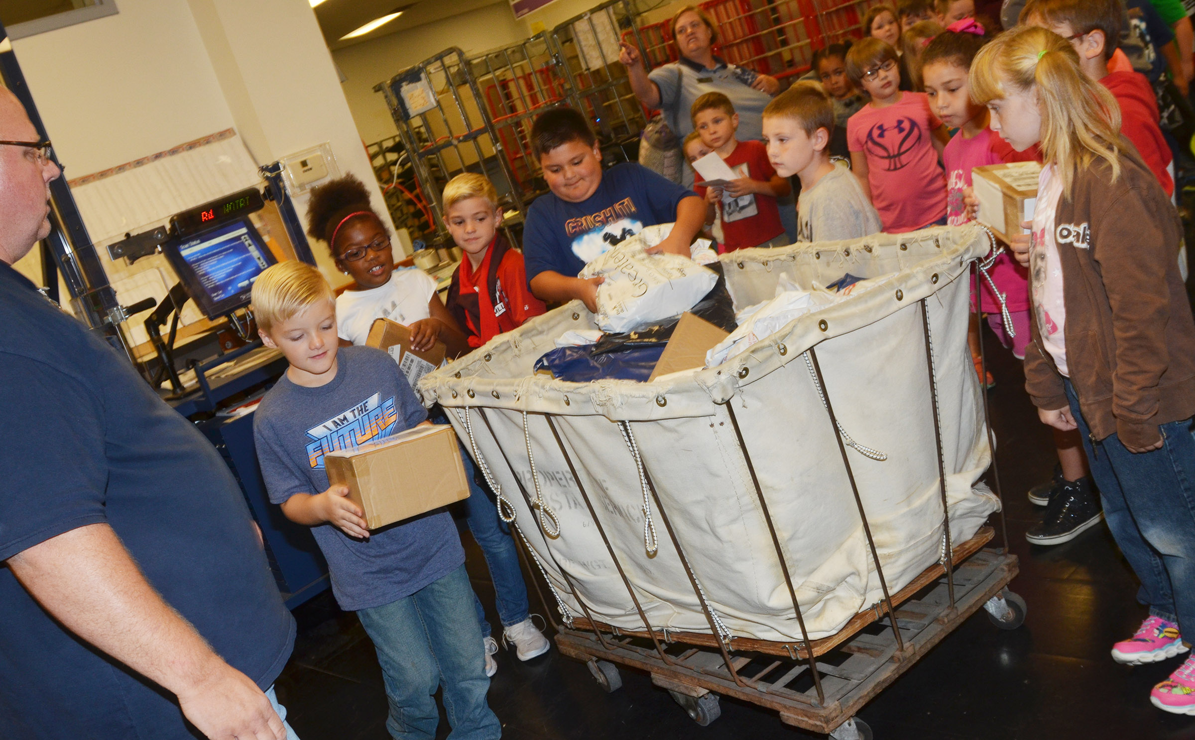 Campbellsville Post Office employee Scott Darst helps CES second-graders sort packages.