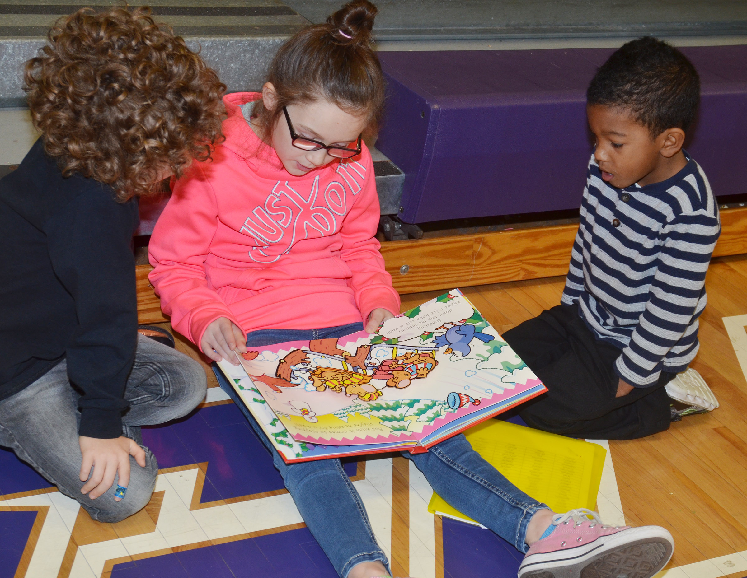 CES second-grader Anna Keith reads to preschool students Zyron Young, at left, and Rakim Dunn.