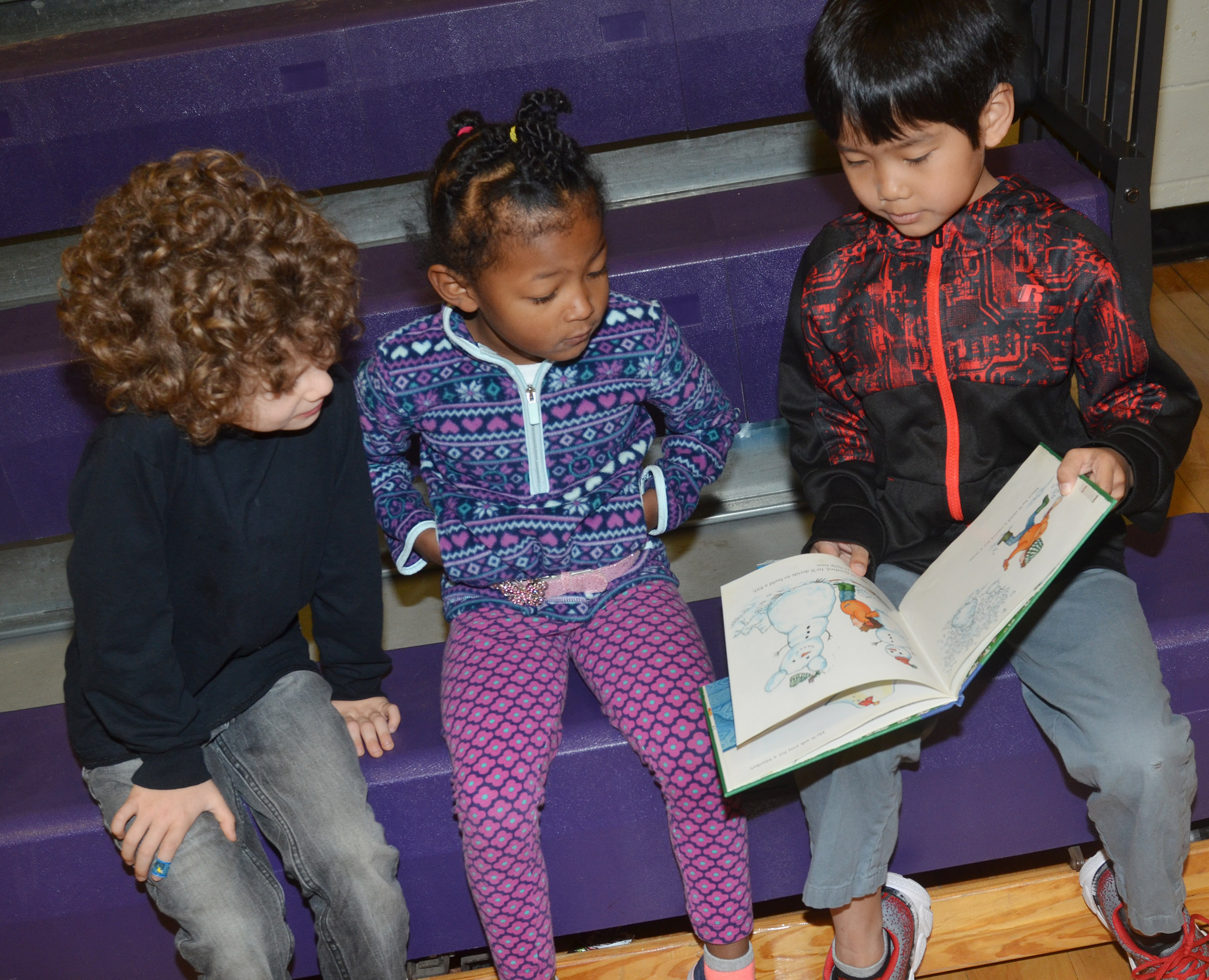 CES second-grader Zach Hak reads to preschool students Zyron Young, at left, and Modesty Taylor.
