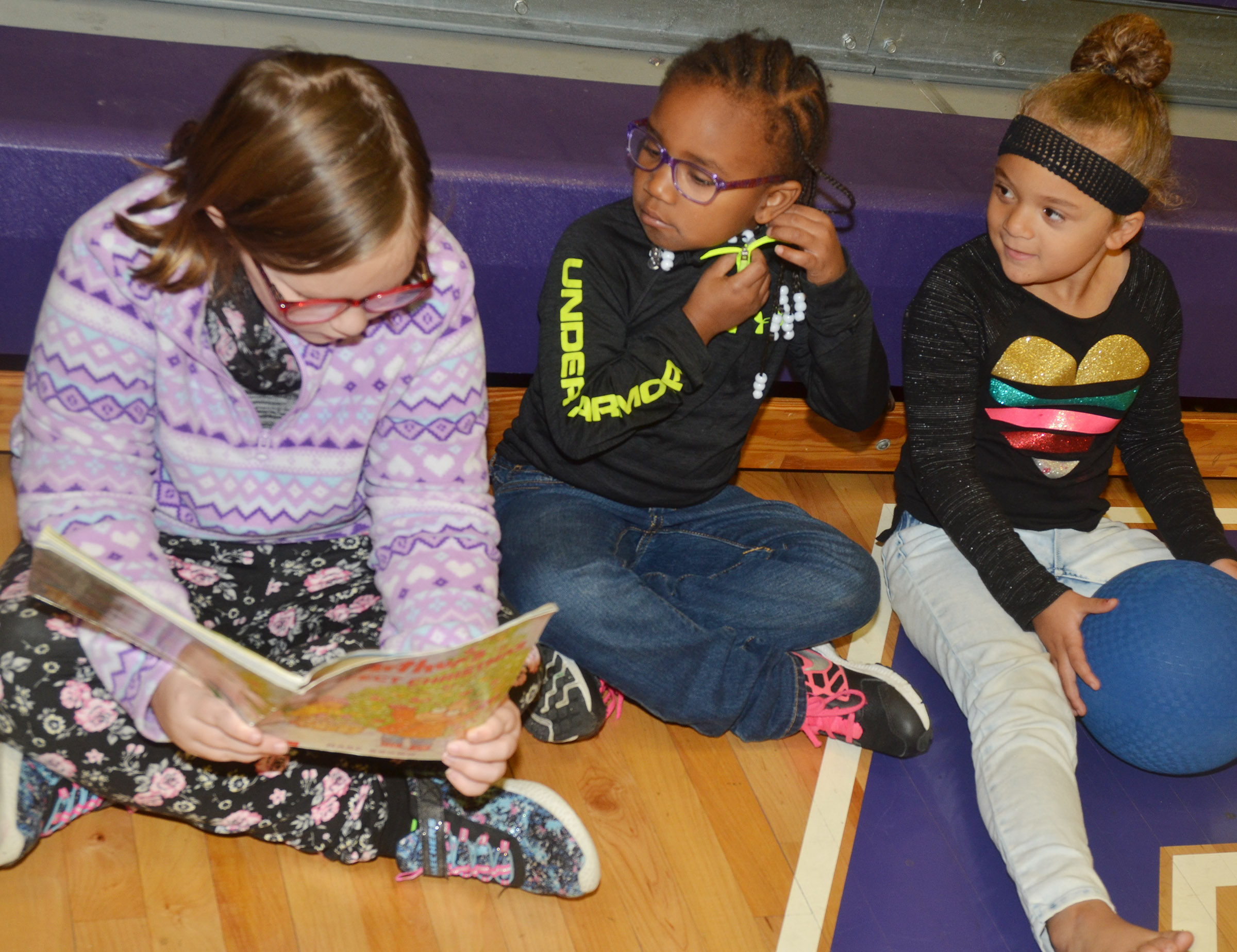 CES second-grader Justice Albrecht reads to preschool student Kyona Mitchell, at left, and Layla Barbee.