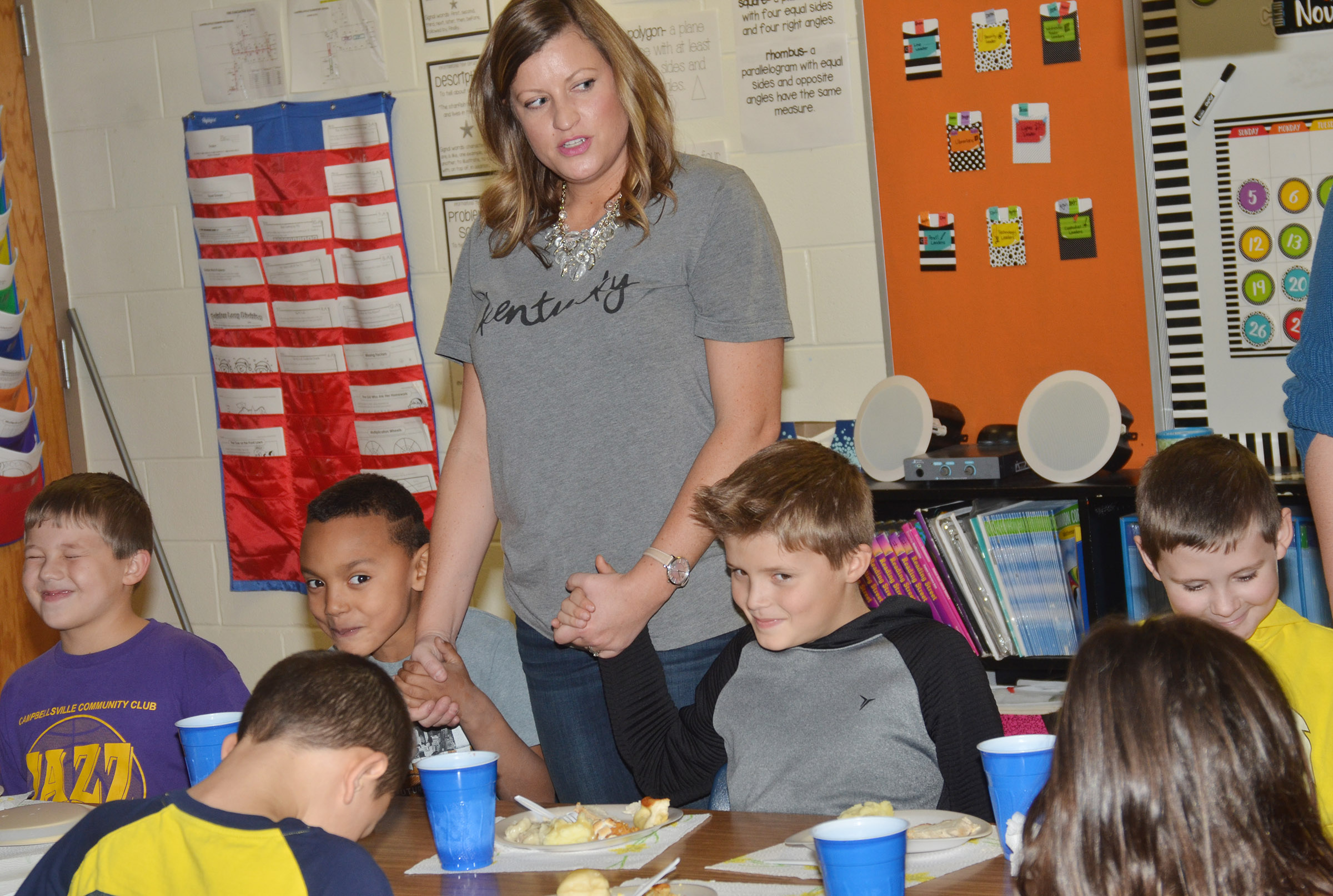 CES third-grade exceptional child educator Ashlee Petett and her students pray together before enjoying their Thanksgiving feast.