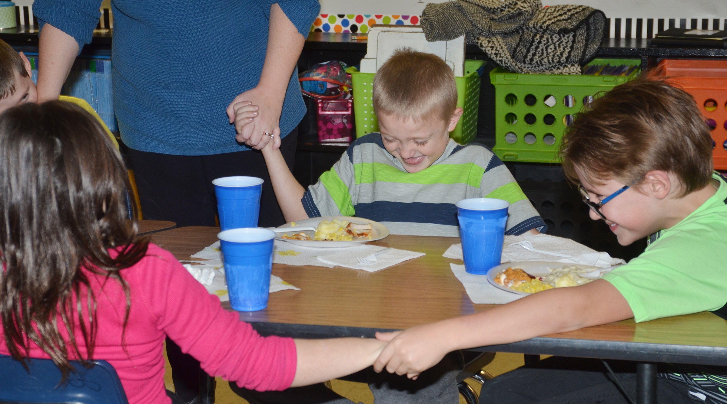 CES third-graders Trenton Harris, at left, and Dalton Shively pray with their classmates before enjoying their Thanksgiving feast.