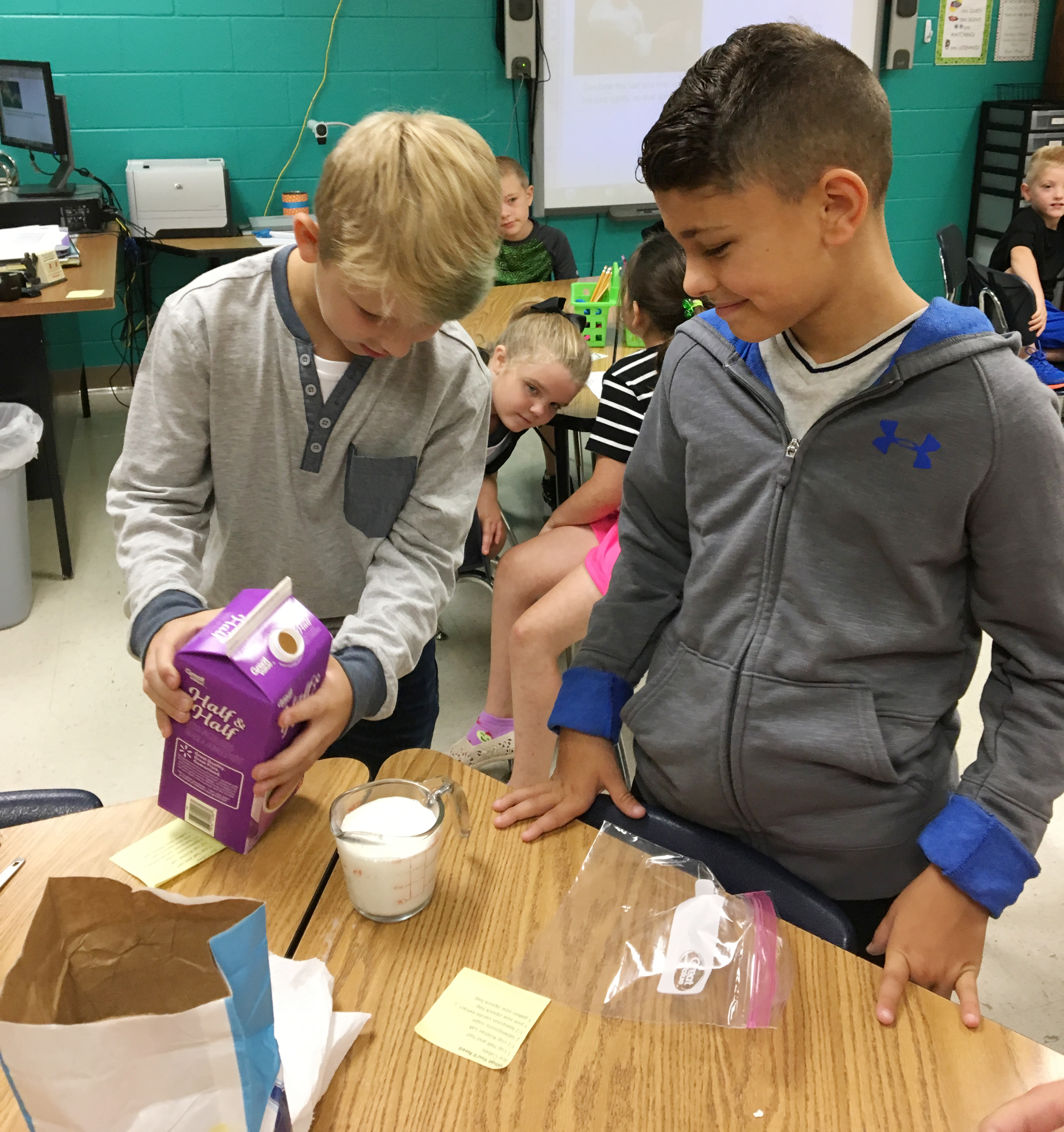 CES third-graders Mason Davis, at left, and Braygon Noegel pour half and half to add to their mixture.