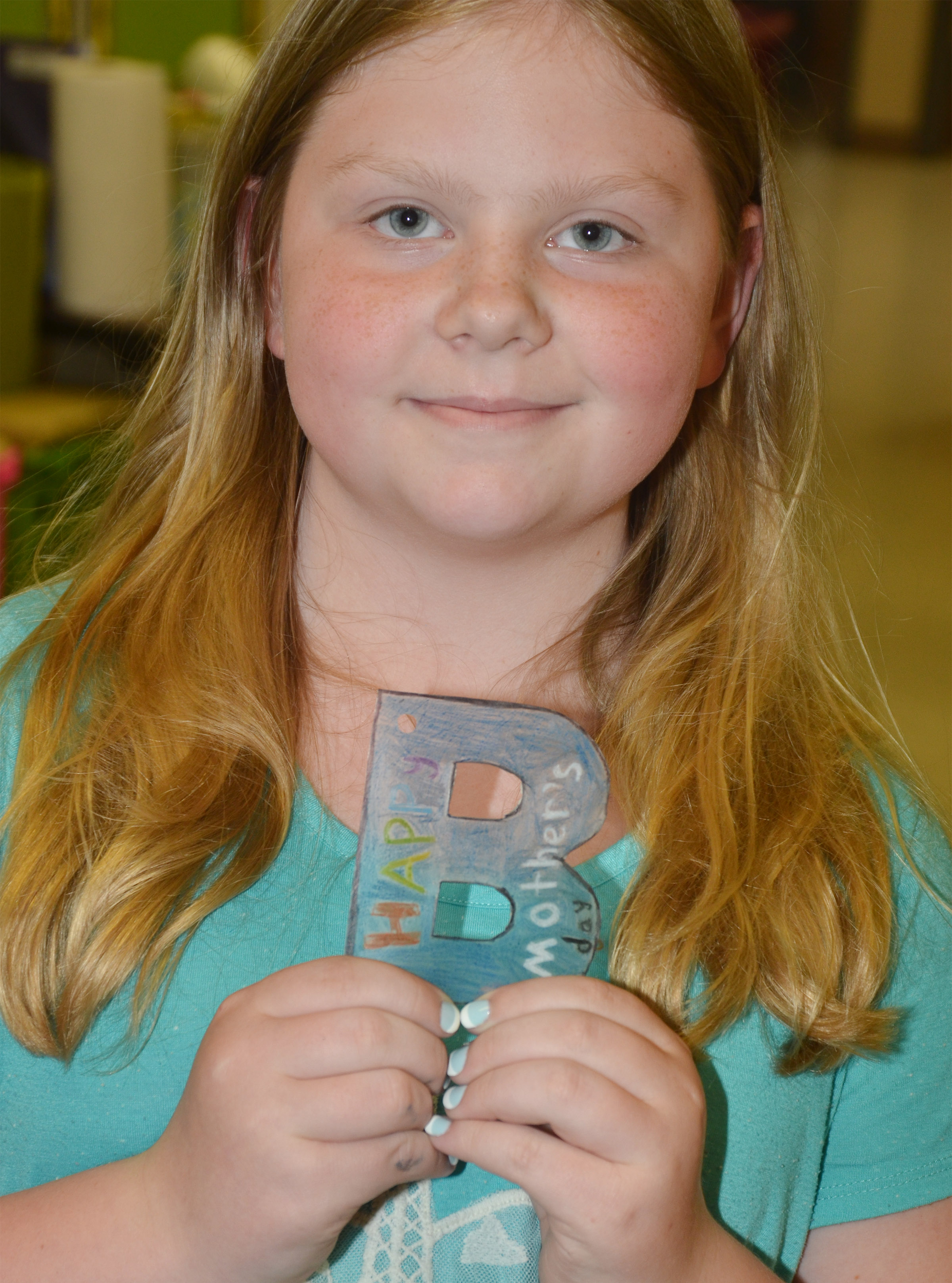 CES third-grader Alyssa Bennett holds what will become a keychain for her mother.