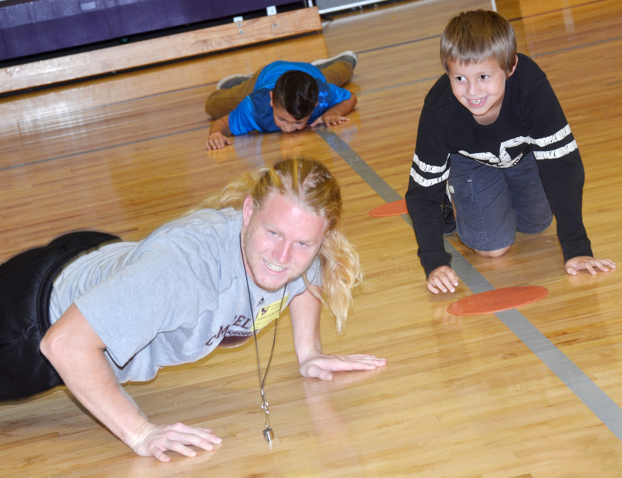 CES third-grader David McFarland does pushups with Campbellsville University student Cruise Coulter.