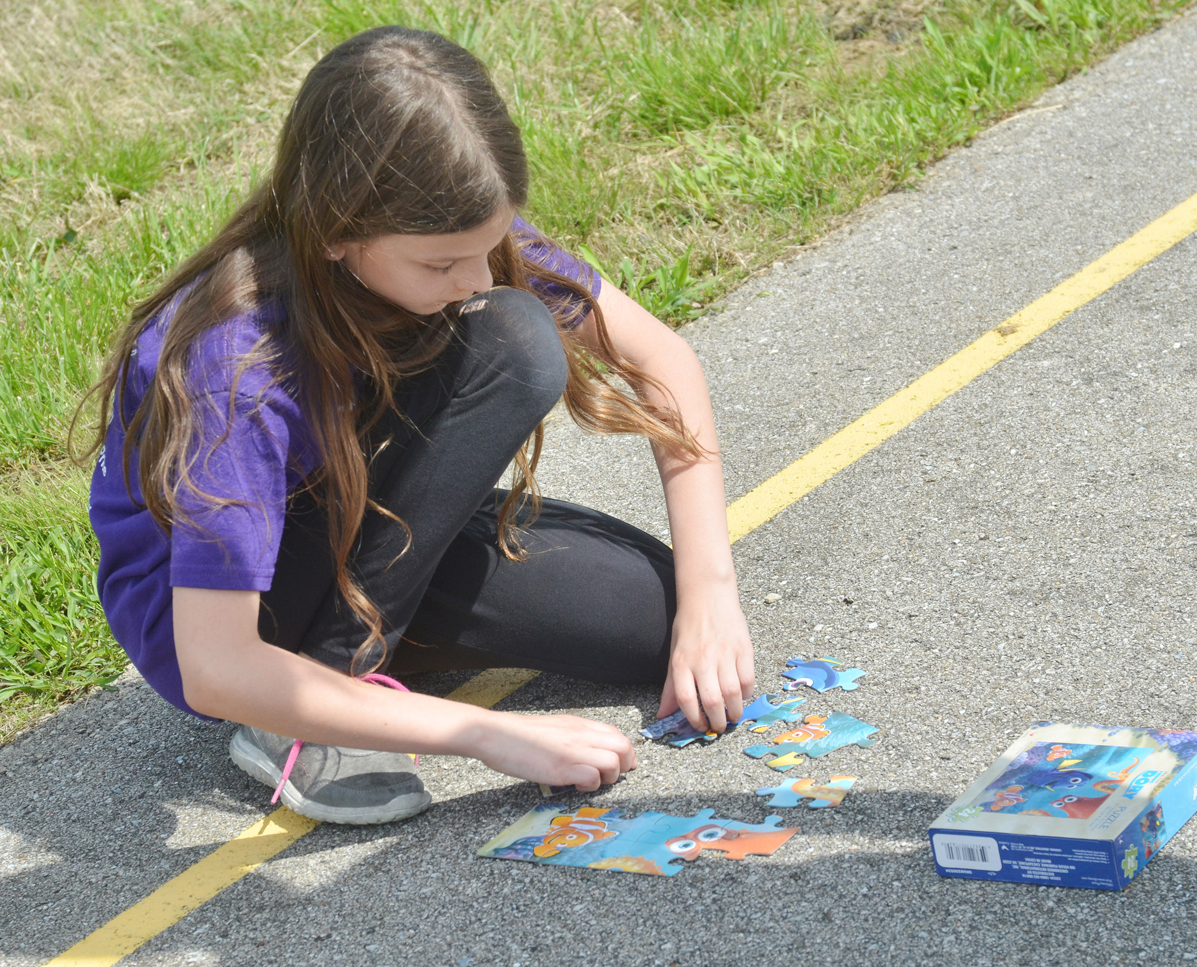 CES third-grader Madie Gebler puts her class's puzzle together.