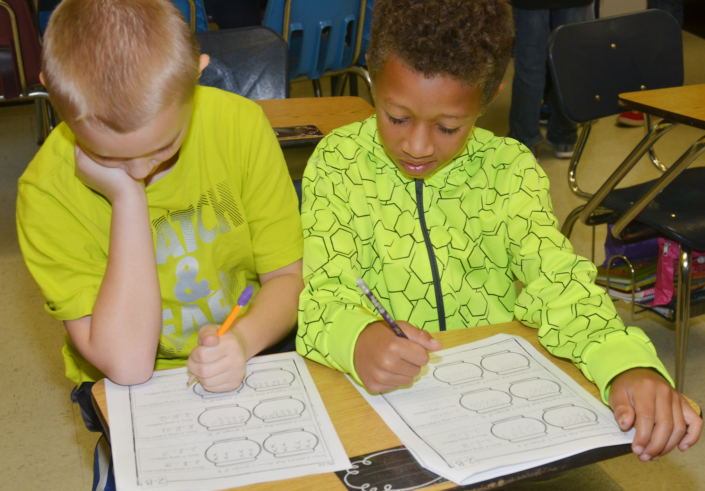 CES third-graders Camren Skaggs, at left, and Rajon Taylor sit together as they work on their multiplication math worksheets.