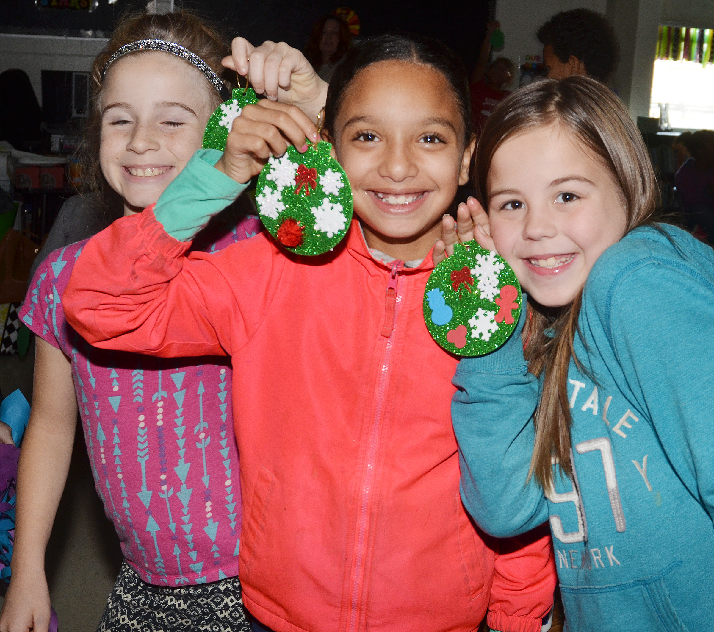 From left, CES fourth-graders Raegan Hayes, Alyssa Knezevic and Chloe Bates hold their ornaments.