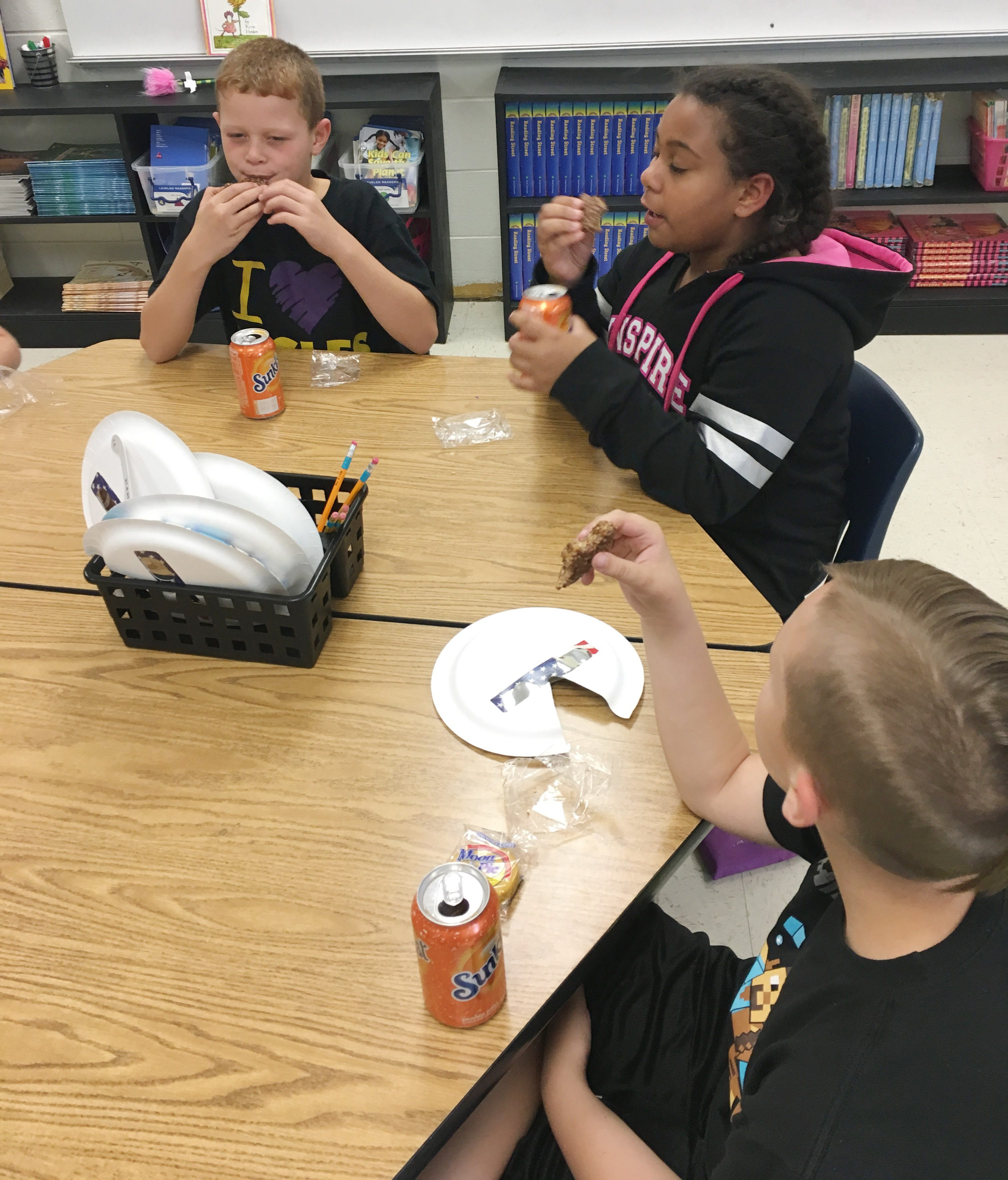 From left, CES fourth-graders Demetrious Dickens, Narissa Barnett and Bradley Paris enjoy their Star Crunch and Moon Pie snacks.