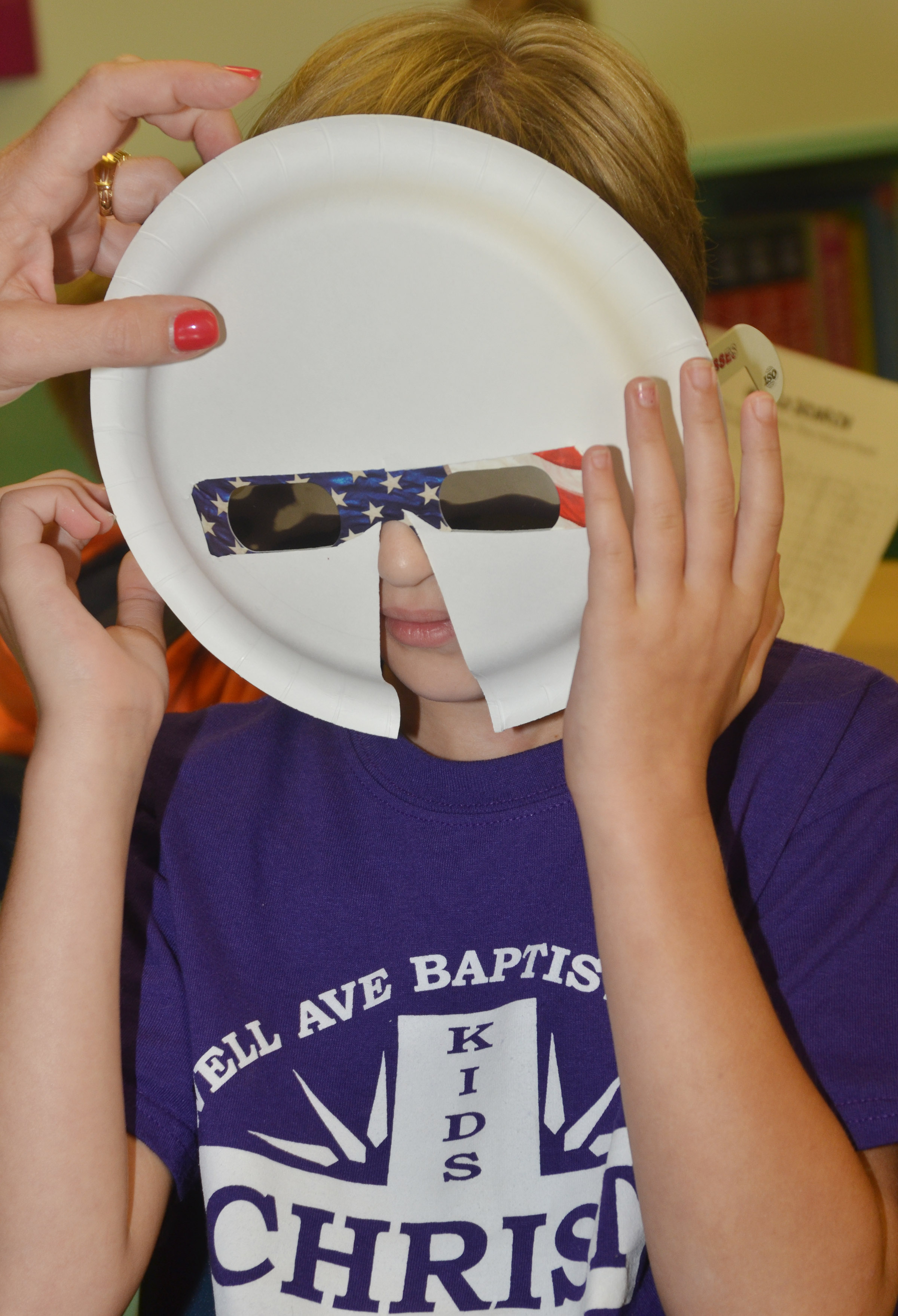 CES fourth-grader Katie Nunn tries on her solar eclipse mask.