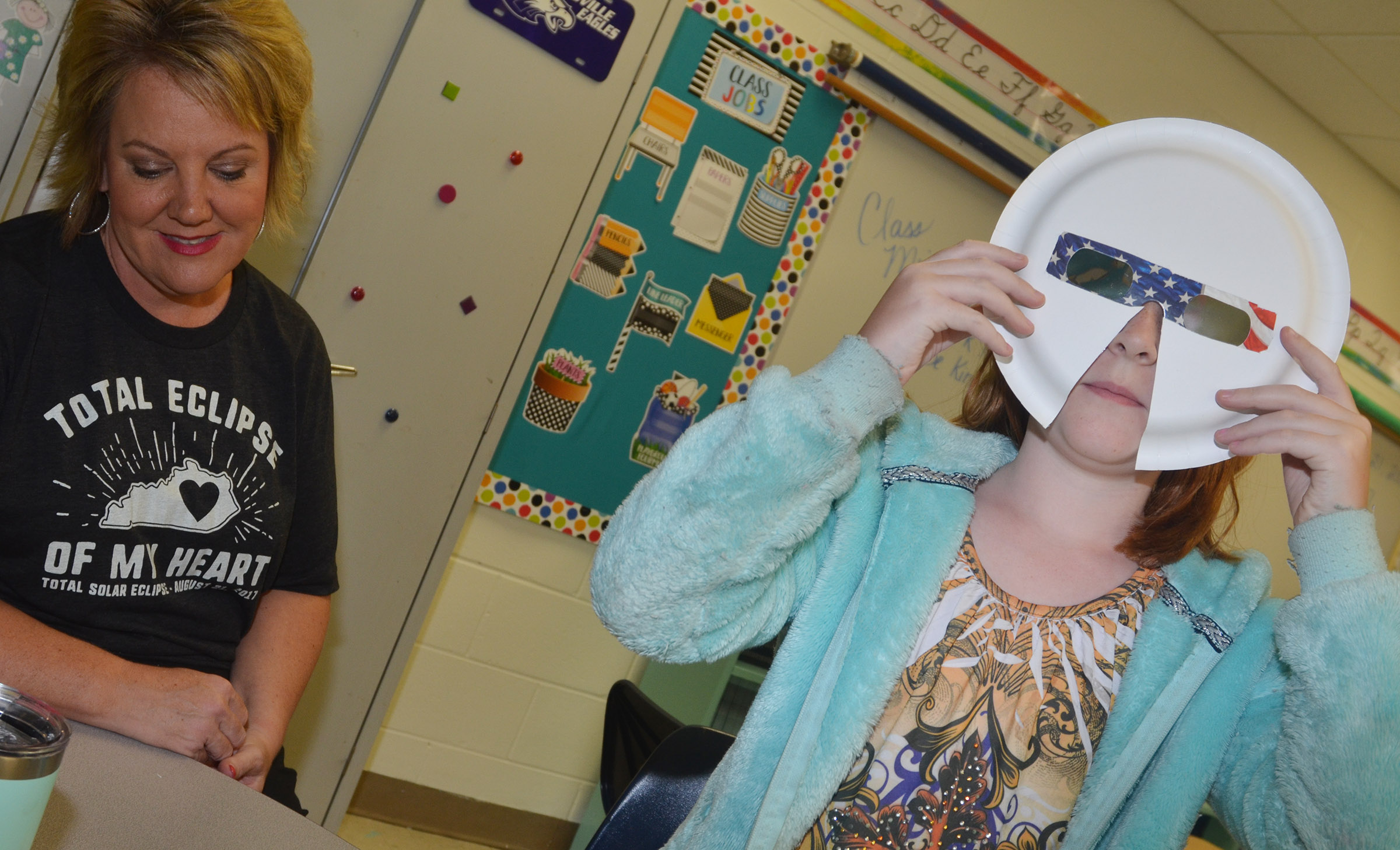CES fourth-grader Nora Harris tries on her solar eclipse mask, as teacher Kaye Agathen watches.